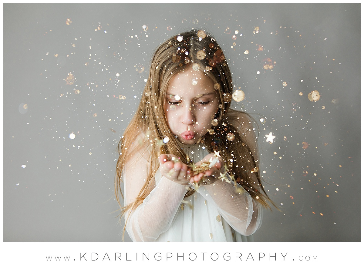 Nine year old girl blowing gold glitter