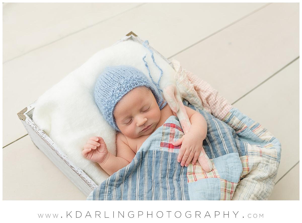 Newborn in white box with quilt