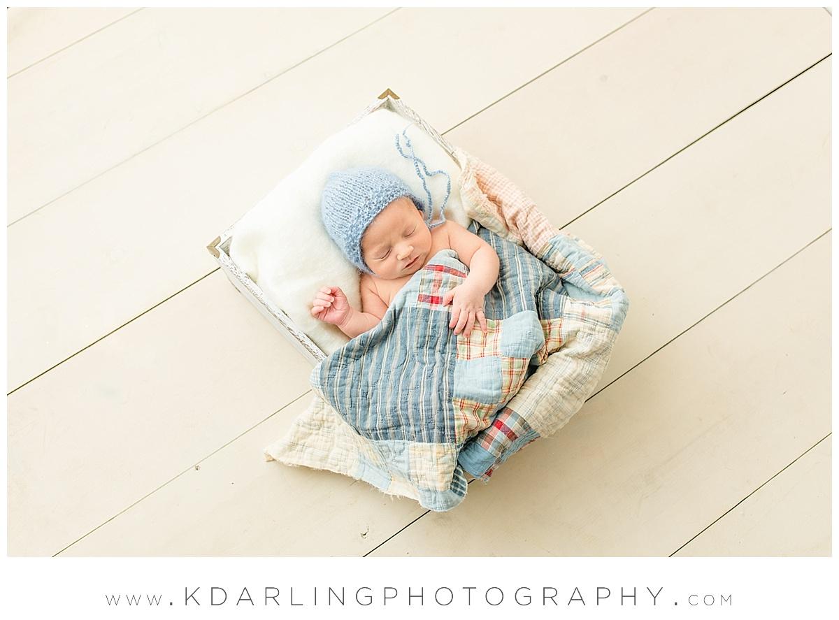 Newborn baby boy on white wood floor