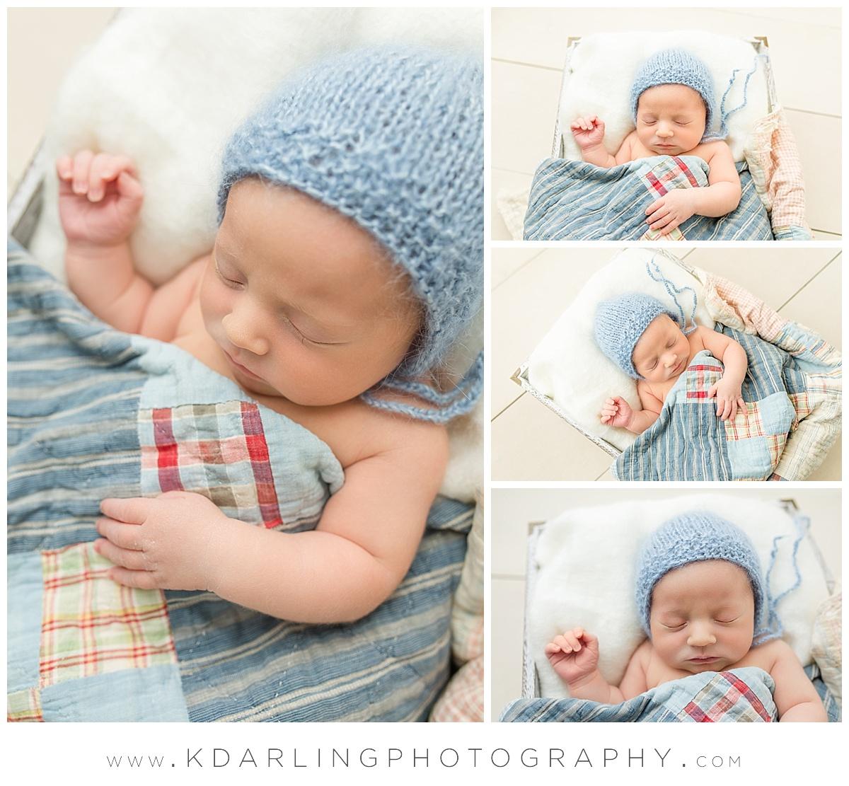 Newborn baby boy in blue bonnet with quilt