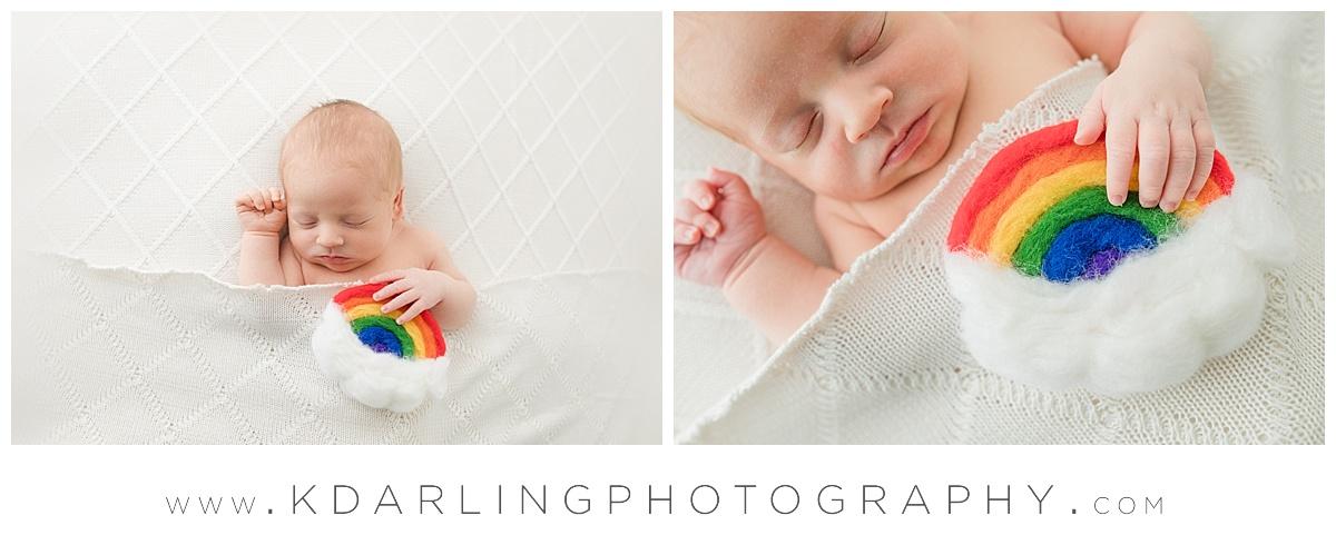 Newborn baby boy holding rainbow