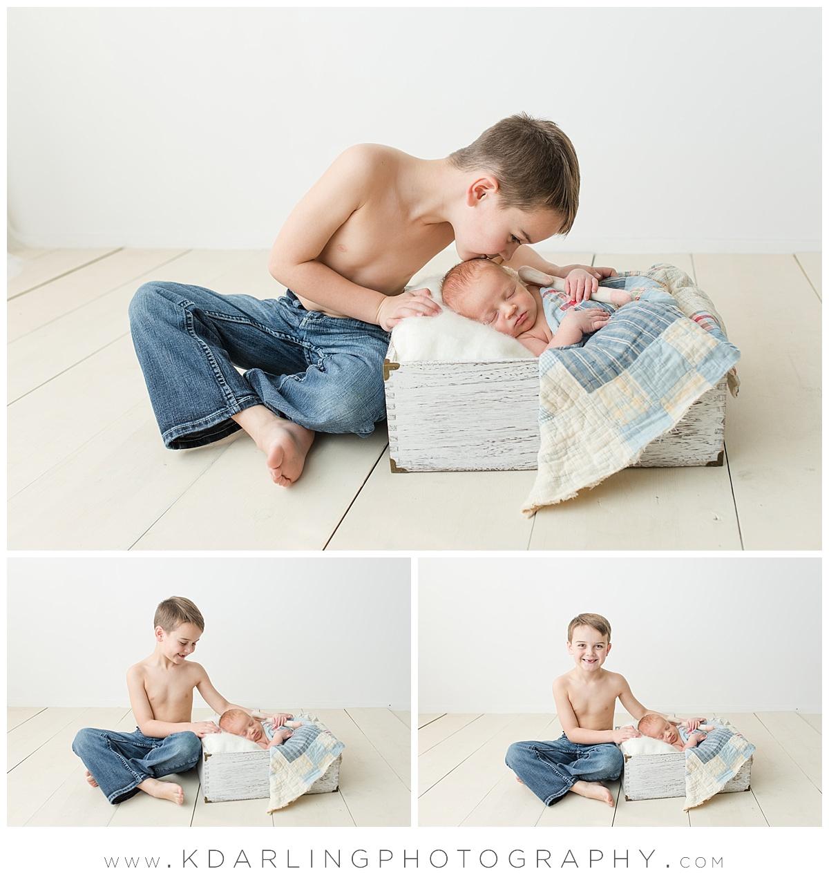 Big brother kissing newborn baby