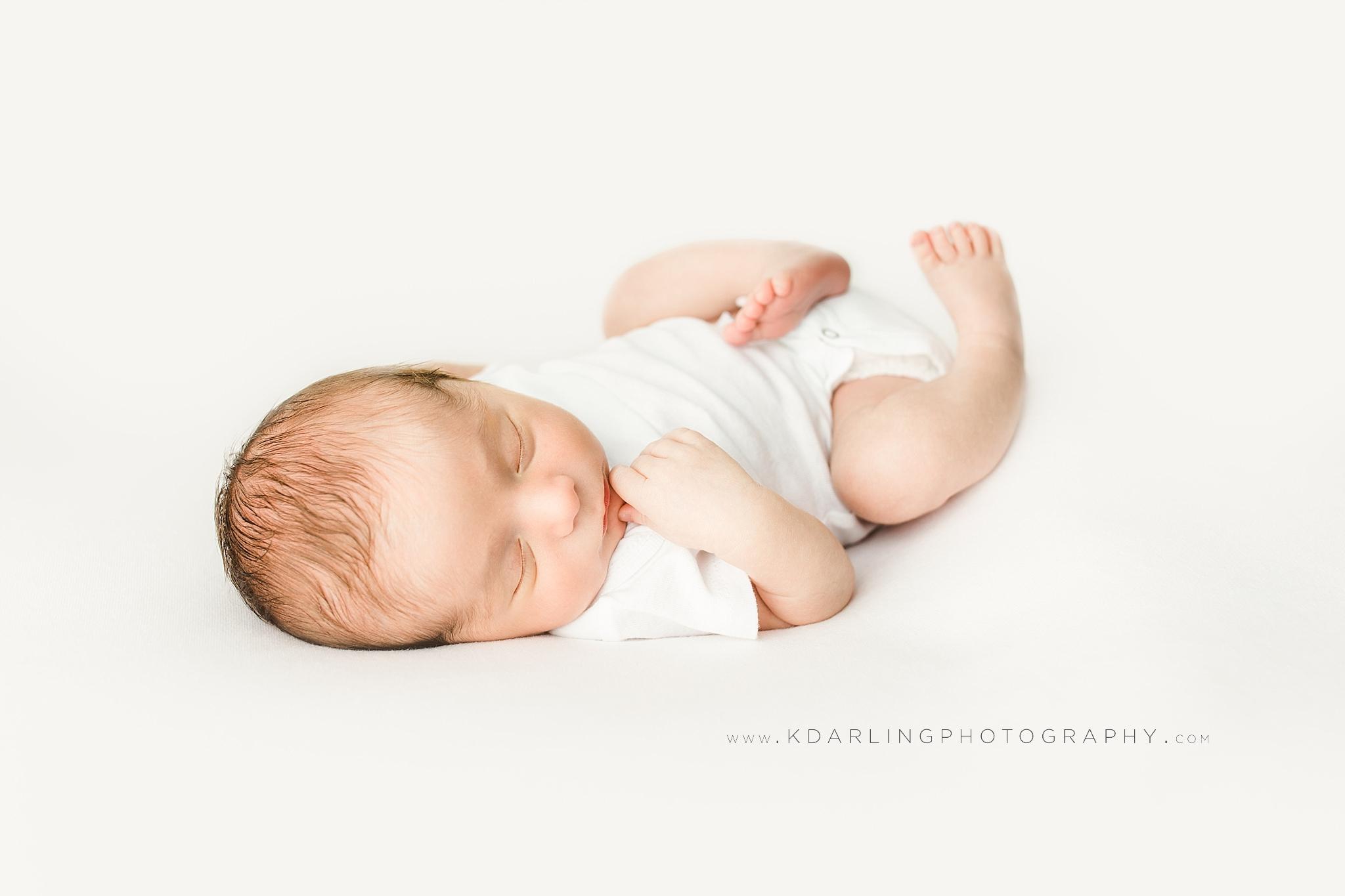 Newborn baby boy sleeping wearing white onesie