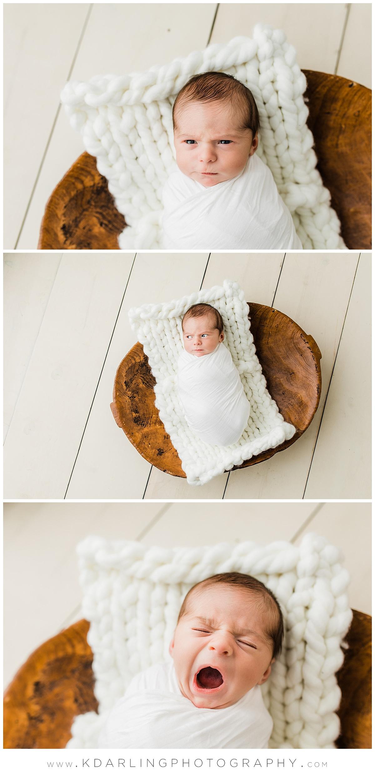 Newborn baby boy in dough bowl yawning