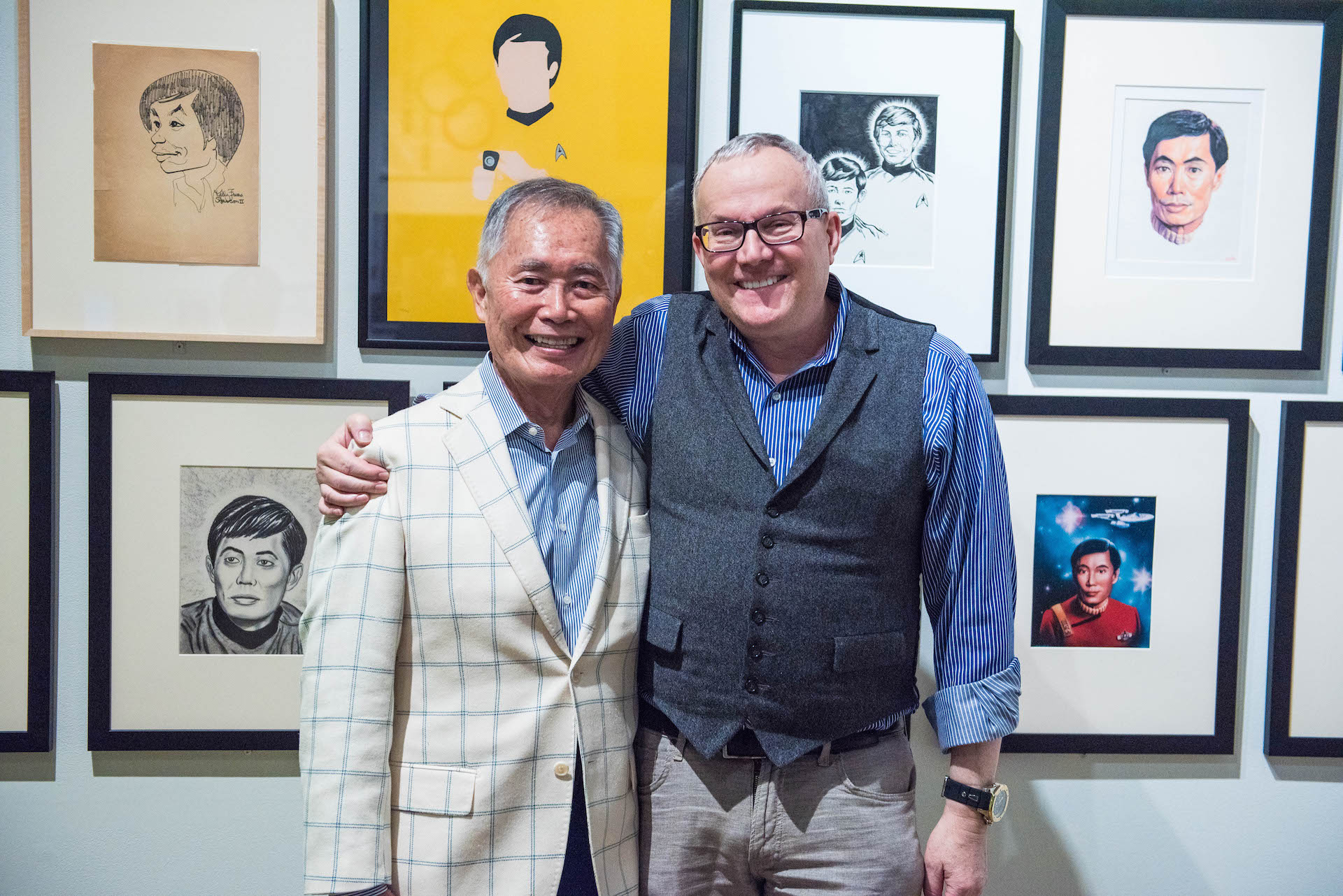 George and Brad Takei grinning in front of fan art.