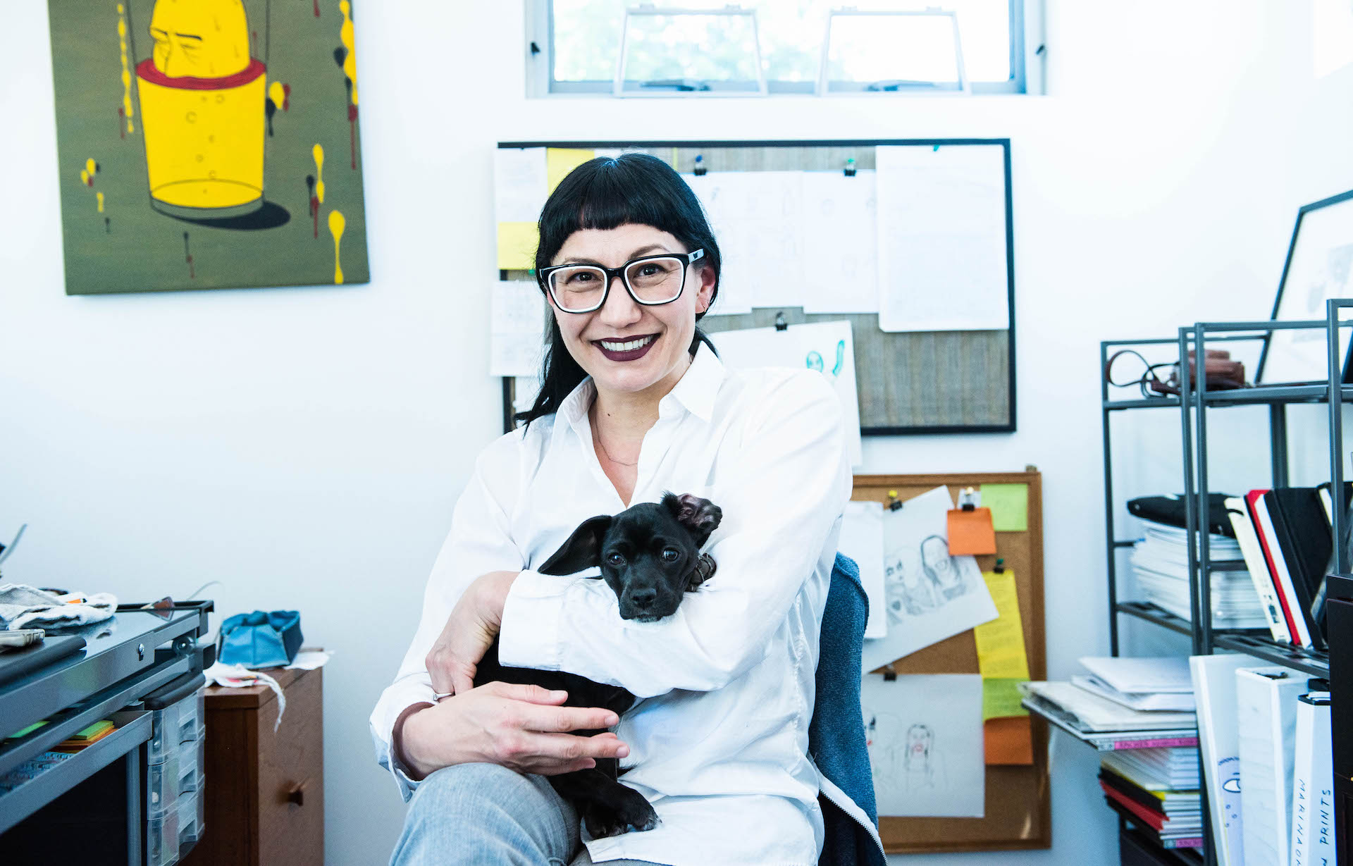 MariNaomi with her puppy in her art studio.