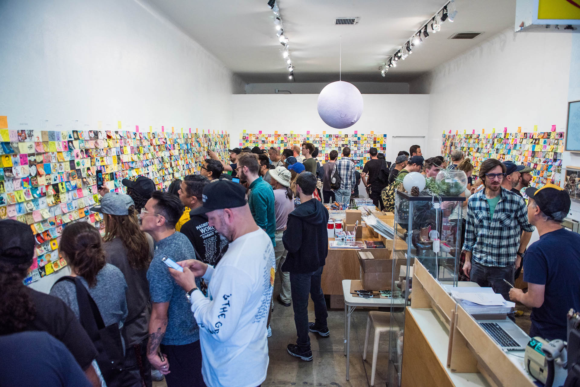 Giant Robot founder Eric Nakamura (right in the yellow-black cap) at the register as patrons jot down the post-its they wish to purchase.