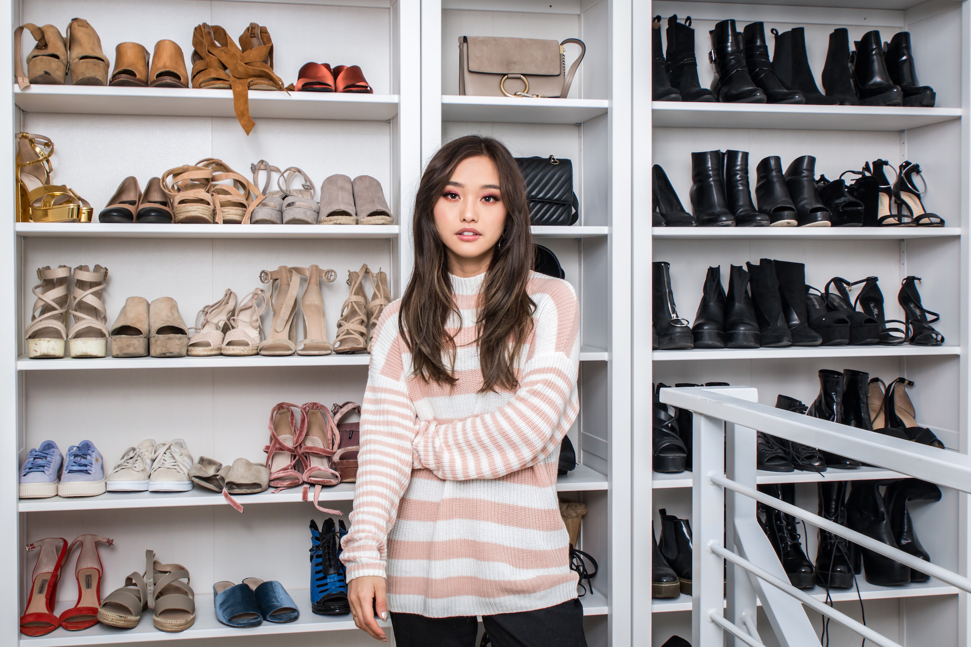 Jenn in her Eggie sweater and with her collection of shoes and bags featured on her YouTube channel, Clothes Encounters.