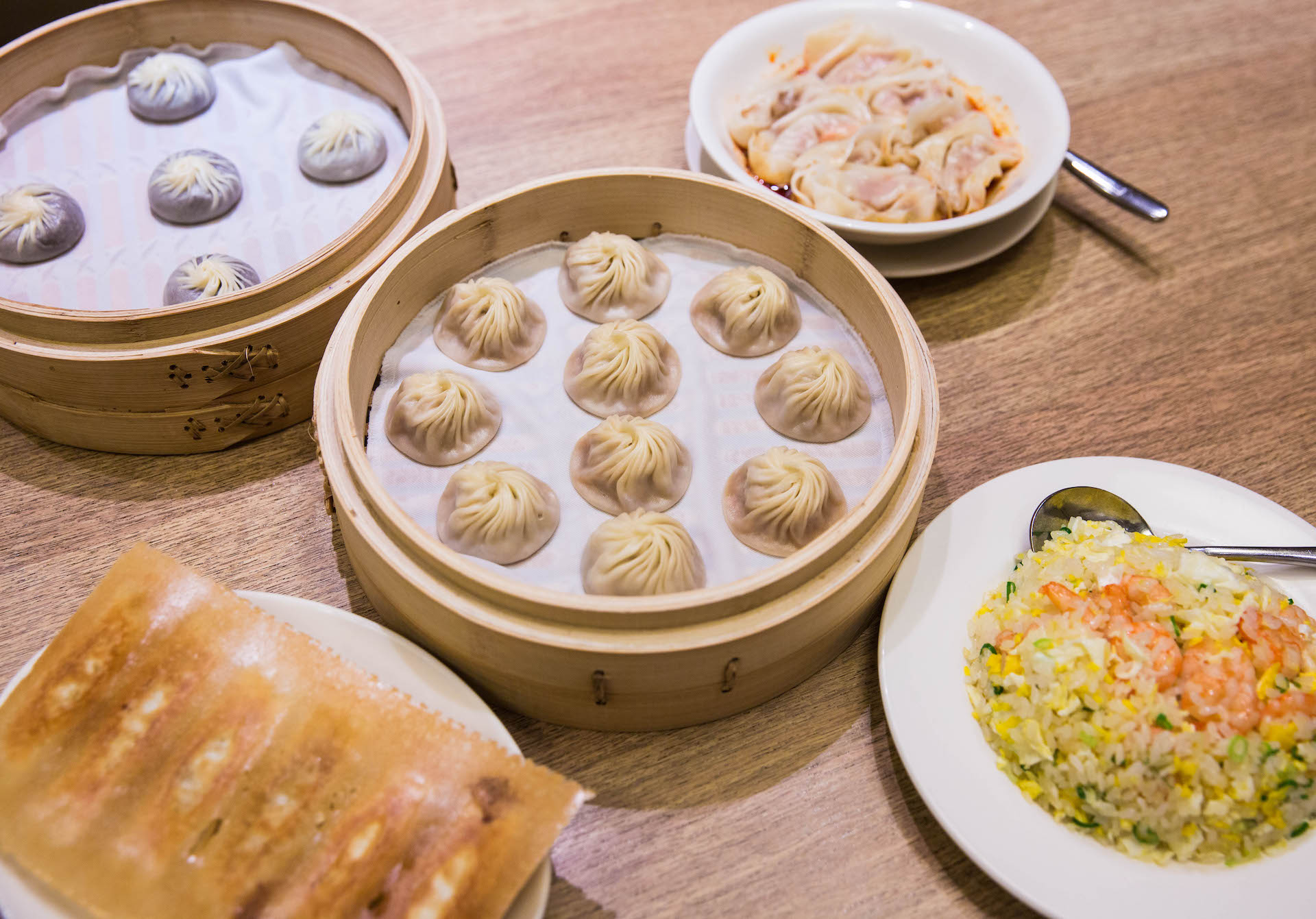 A sample spread. In the middle, the famous soup dumplings. From the left going clockwise, spicy wontons, shrimp fried rice, pot stickers, and red bean dumplings.