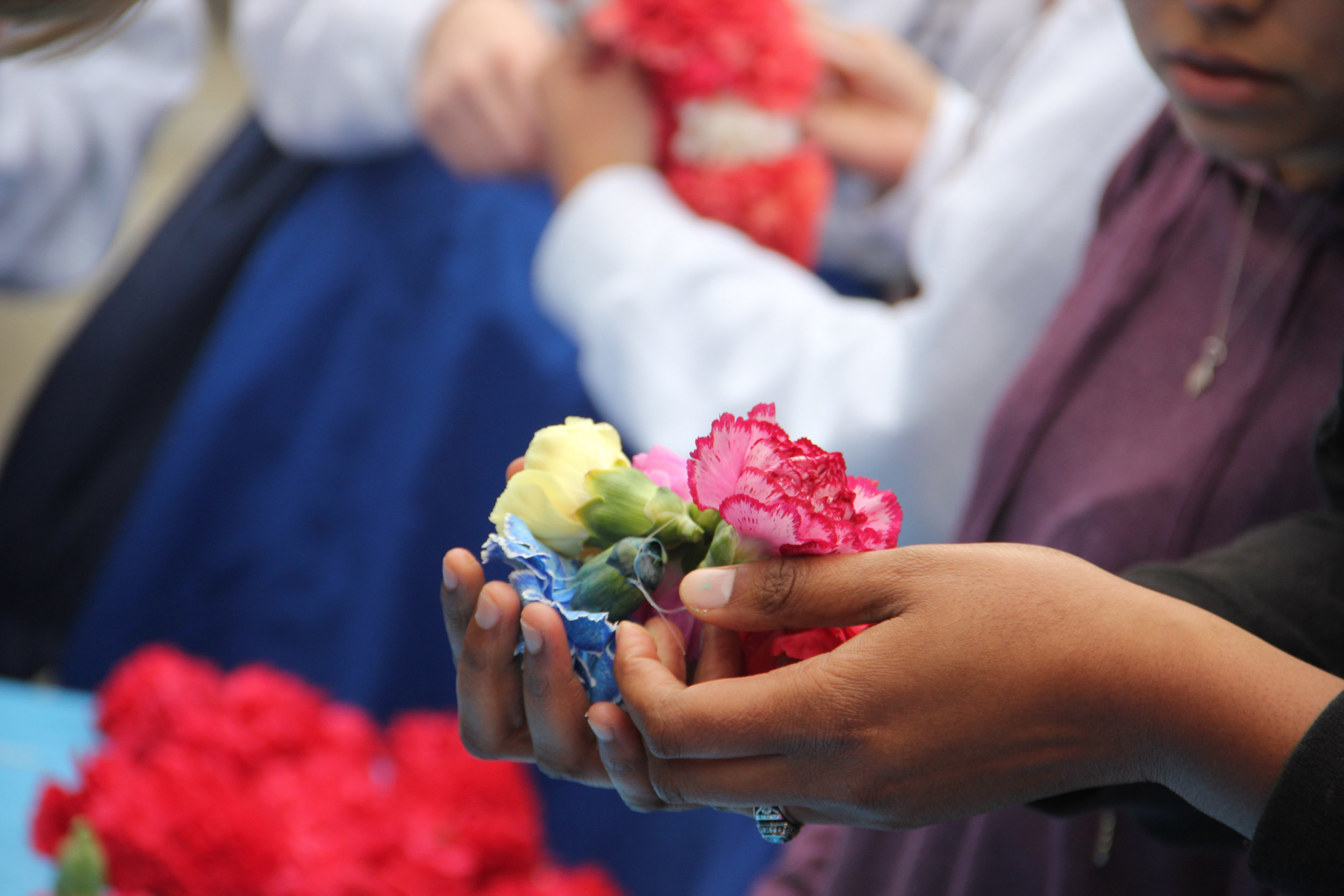 PHOTOS BY NATHAN ACUÑA LEI YOUR LOVE: WC community members gathered around a table to craft dozens of leis of soft-toned flowers.