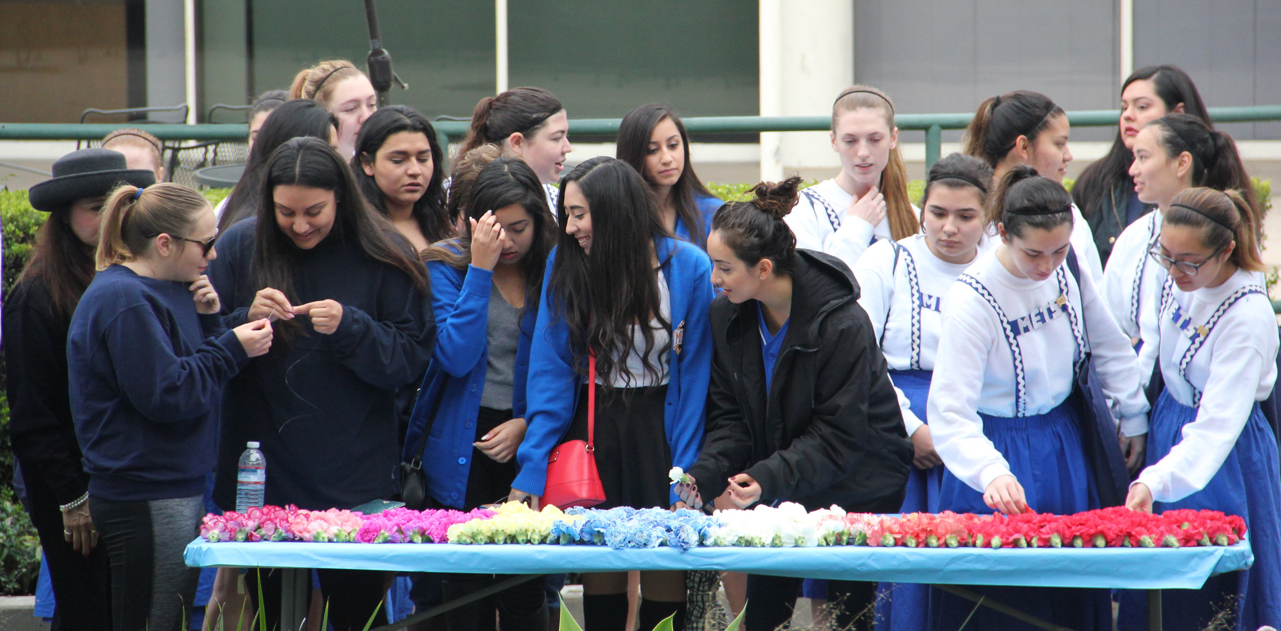 Metaphonian Actives and proteges pause at the lei table and start the lei line.