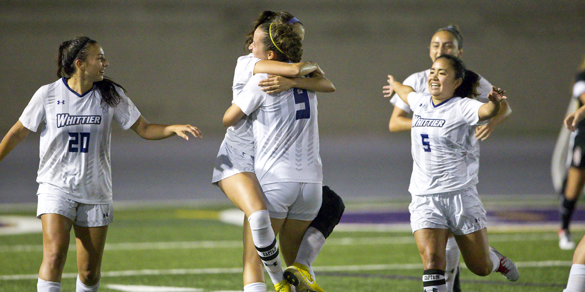 Whittier College players embracing each after a goal