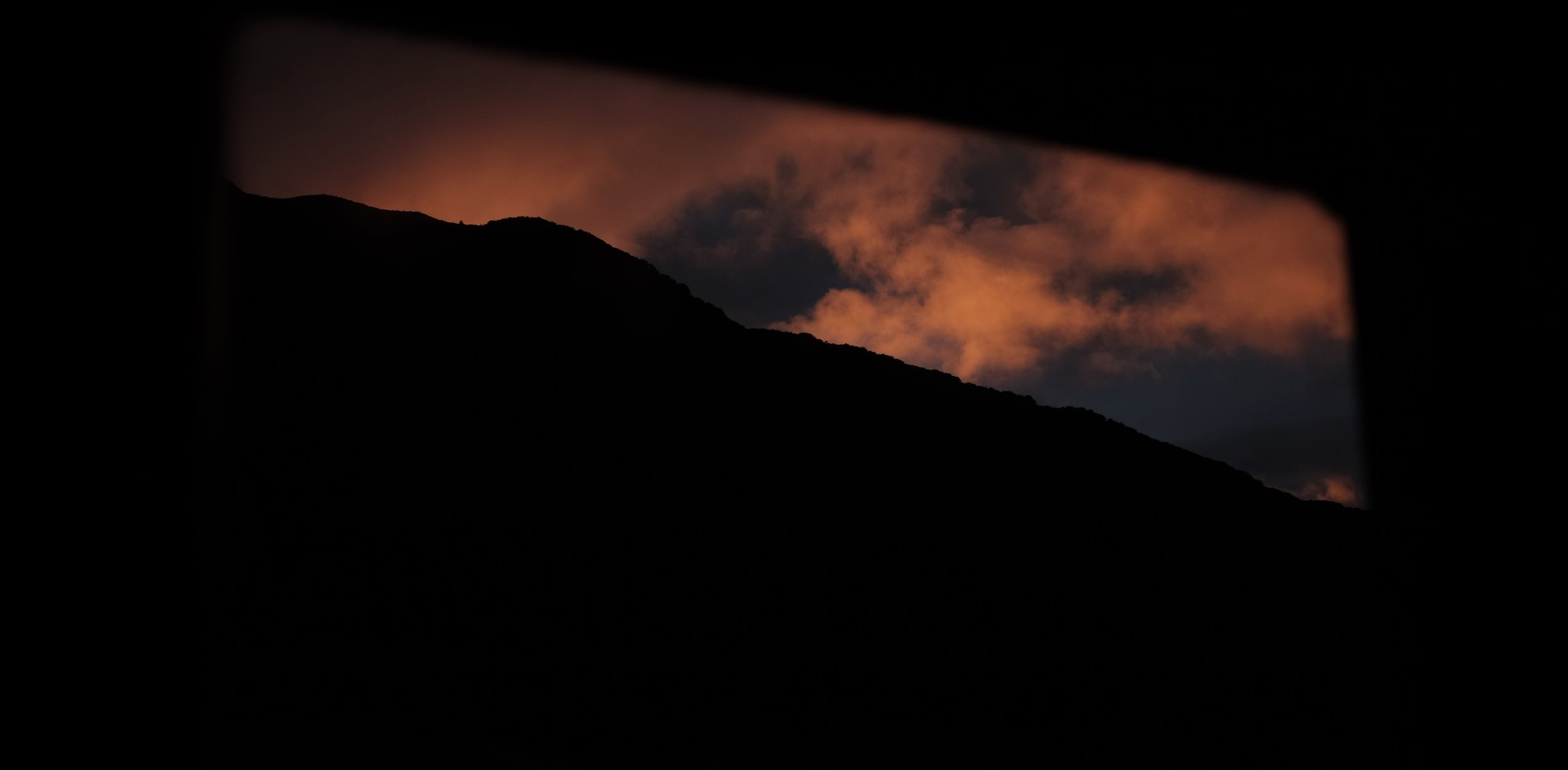 The sun rises outside Aparima Hut in the Takitimu Forest.