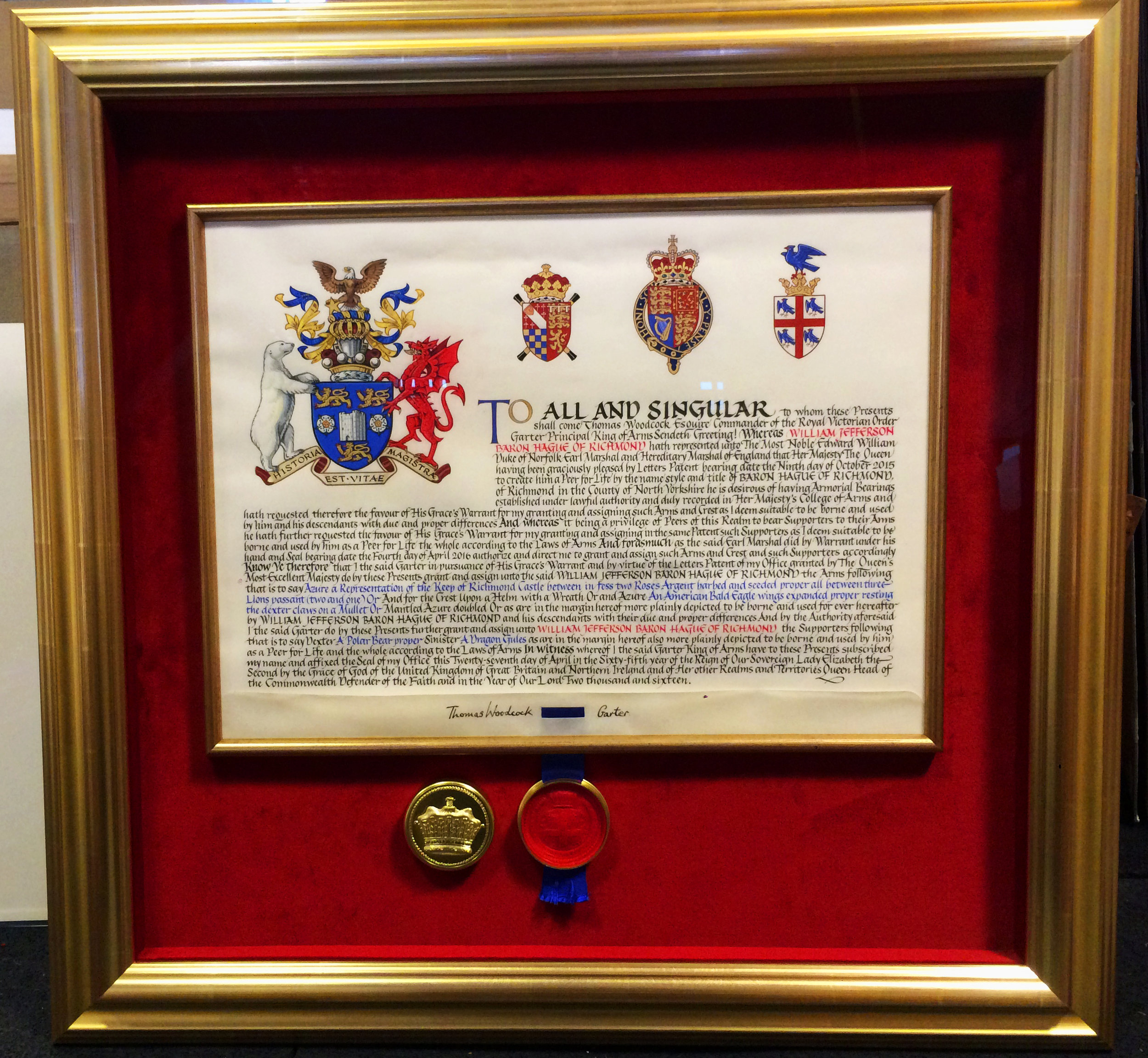 Red velvet wrapped mount for Lord Hague of Richmond. The vellum is held in place behind the edge of the inner gold frame, and the glass is held away from the surface by velvet wrapped spacers. Museum anti-reflection glazing and with UV protection.