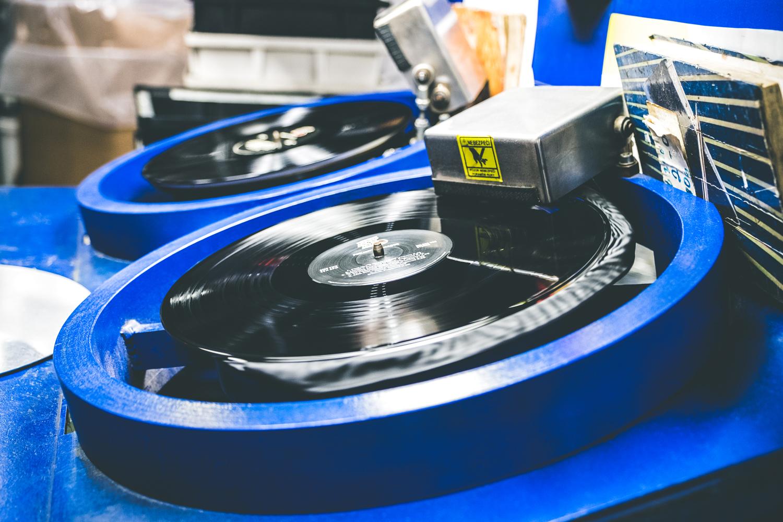 Lisování desky: Vinylový koláček mezi papírovými etiketami v lisu. Následuje ořez přebytečné hmoty.