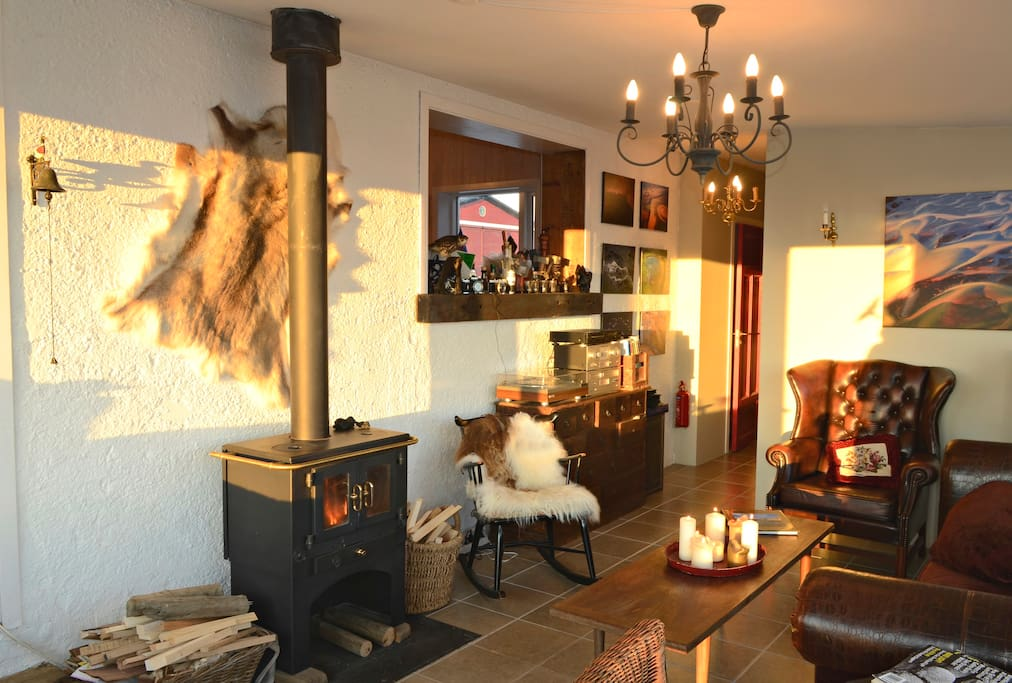 The common living area at the Hrifunes Guesthouse, complete with a cozy fire and a record player. Image c/o    Airbnb   .
