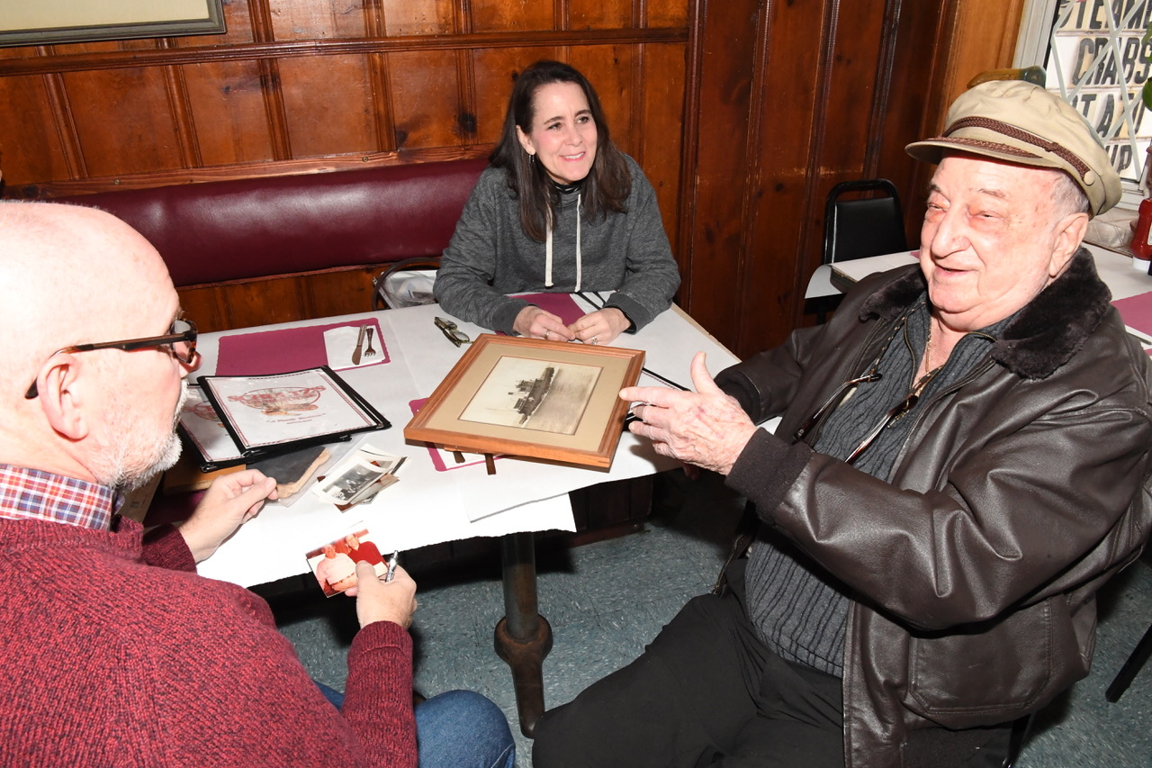 Bobac (right) looking at photos with Millard Hart, and Suzanne Hart Burger (Photo by Jim Burger)
