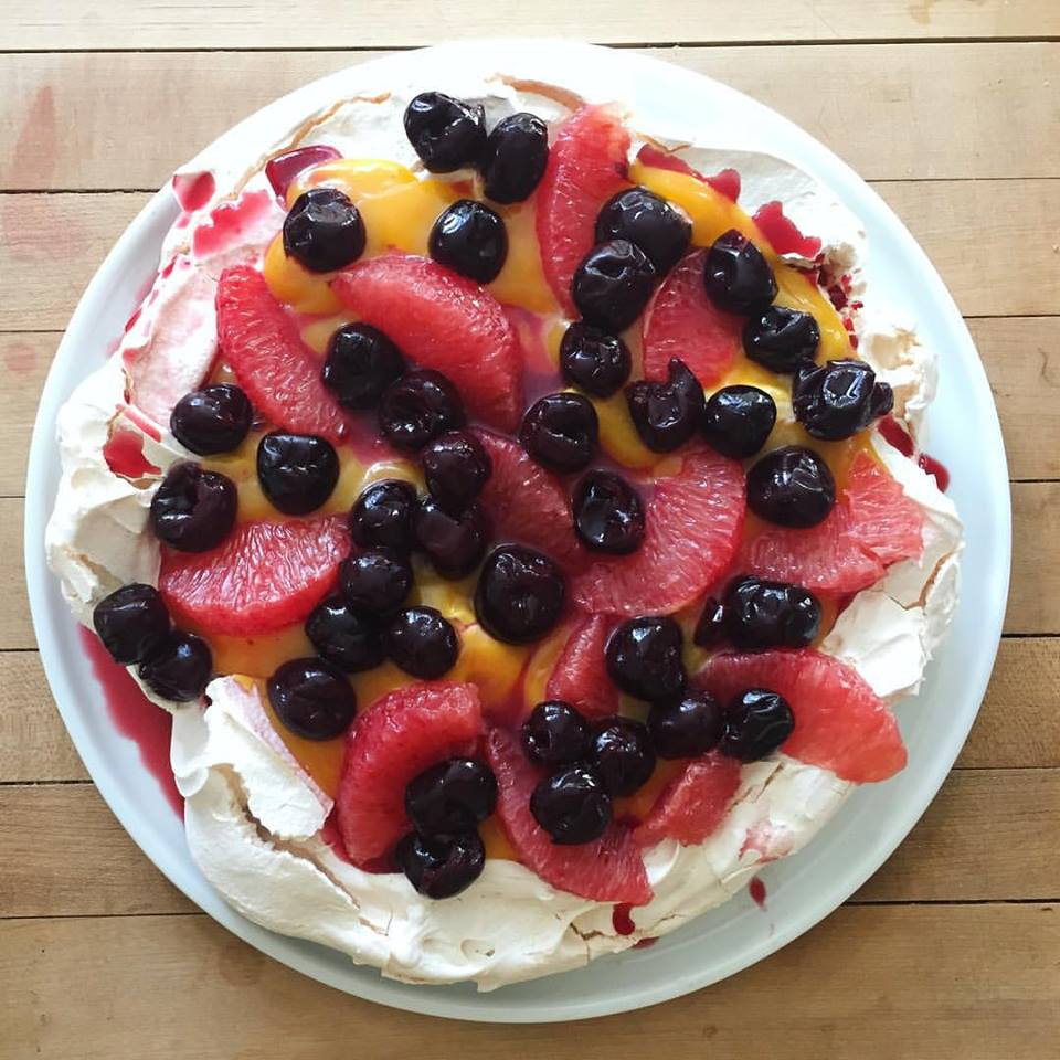 Pavlova (crisp meringue) piled with fresh pink grapefruit curd, grapefruit sections and cherries.