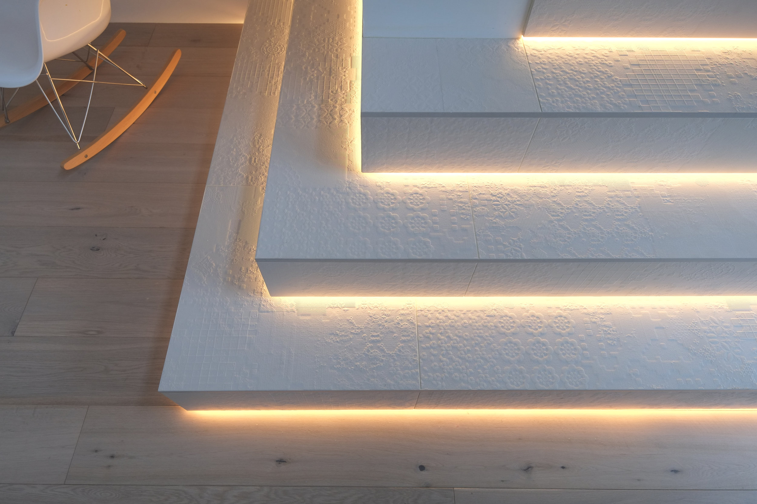Architectural Elements - Porcelain is an excellent material for cladding staircases and architectural elements. We clad the first three steps of this staircase in 10mm Dechirer 1200x1200 by Mutina. A tile characterised by the pattern and depth of texture which is highlighted further by the recessed LED lighting. We supplied the technical drawings as well as the installation.Tile featured: Mutina Dechirer