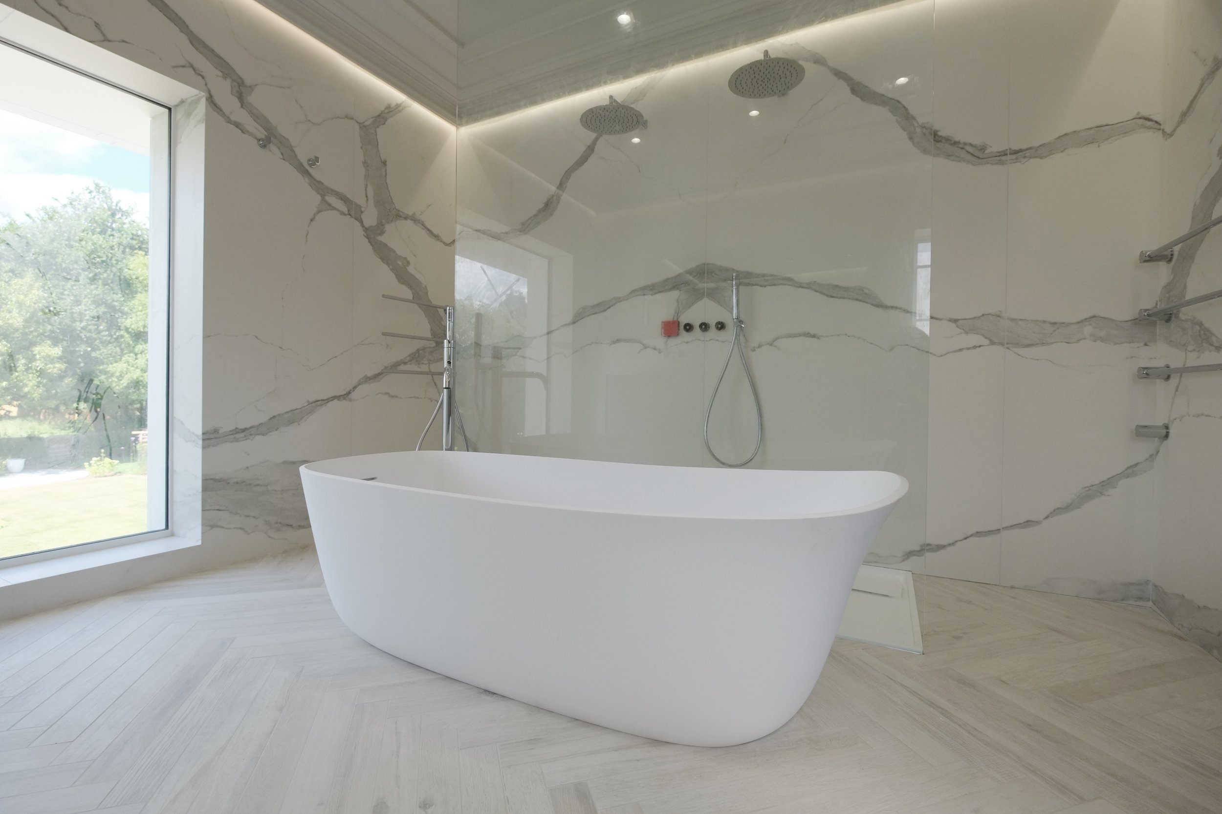 Tiles featured: walls: I Classici di Rex Statuario soft; floor: Wood of Cerim waterjet to create herringbone