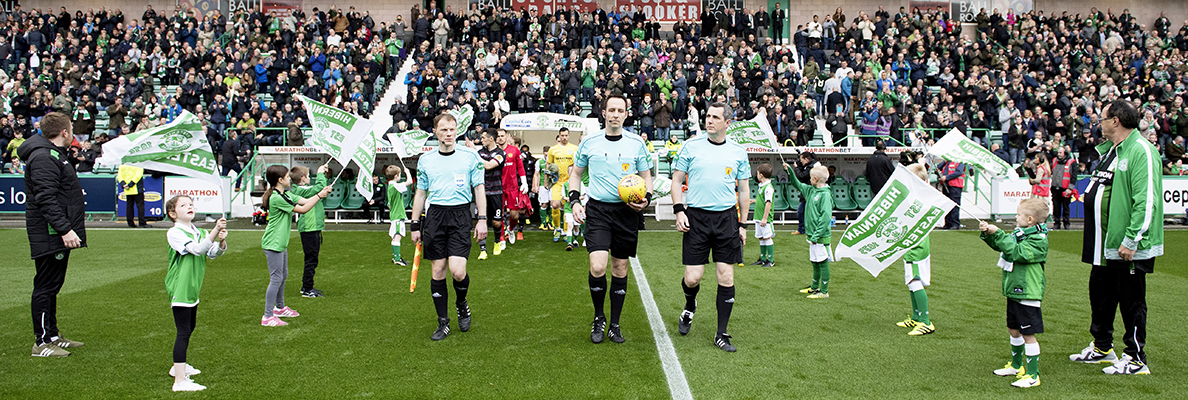 Hibernian Football Club players take to the pitch, waved on by their flag bearers. Image by  hibernianfc.co.uk