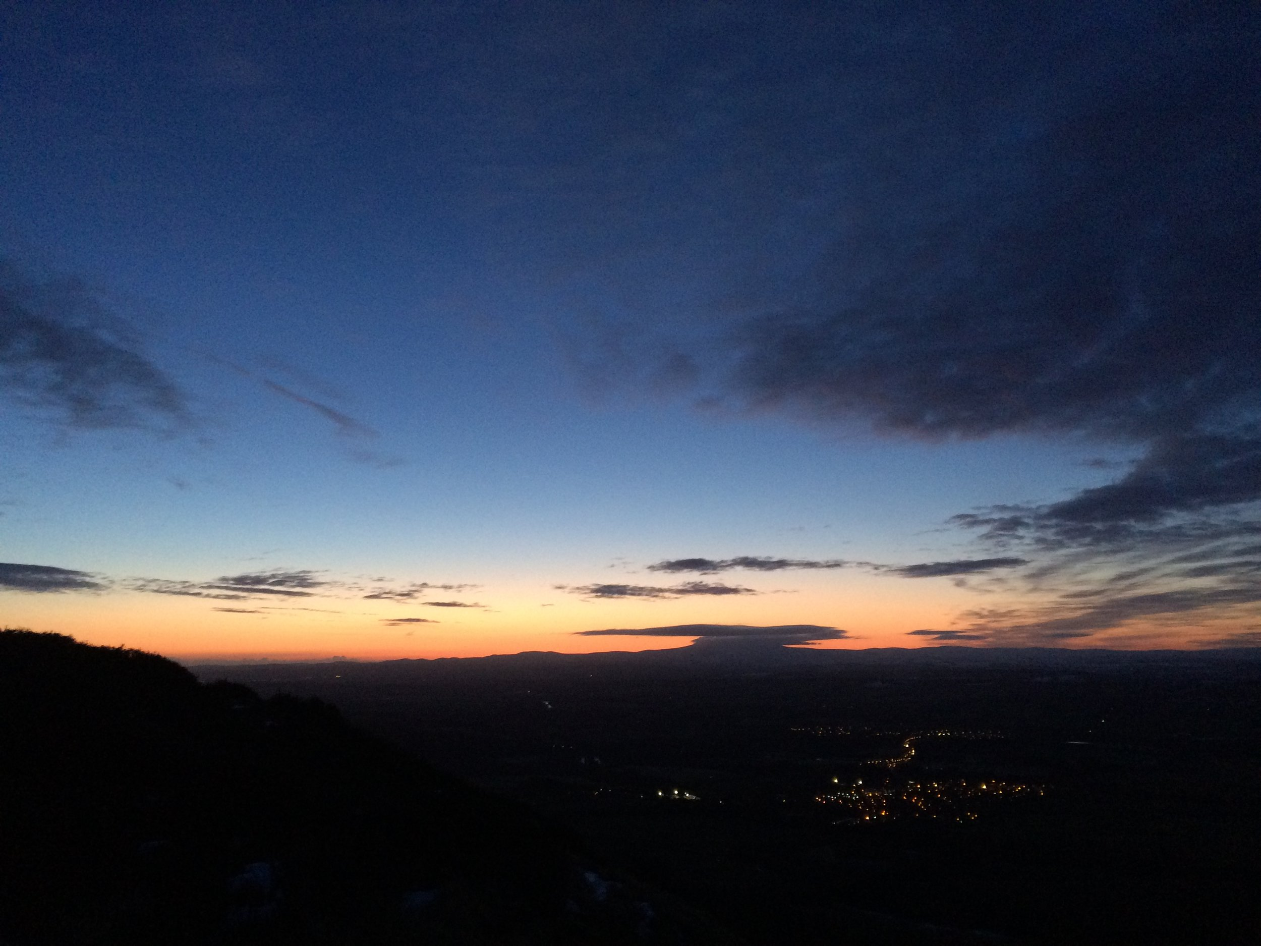 The sun rising over The Cheviot from the eastern top of The Eildons. The lights of Newtown St Boswells seen below.