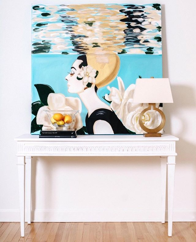 The Lilly Console, named for the floral motif along the apron, features Swedish Gustavian style carvings and a multi-layered finish with warm white tones. Also available as a demilune! Styled here with a gorgeous painting by the talented fellow New Orleanian, @ashleylongshoreart 💙