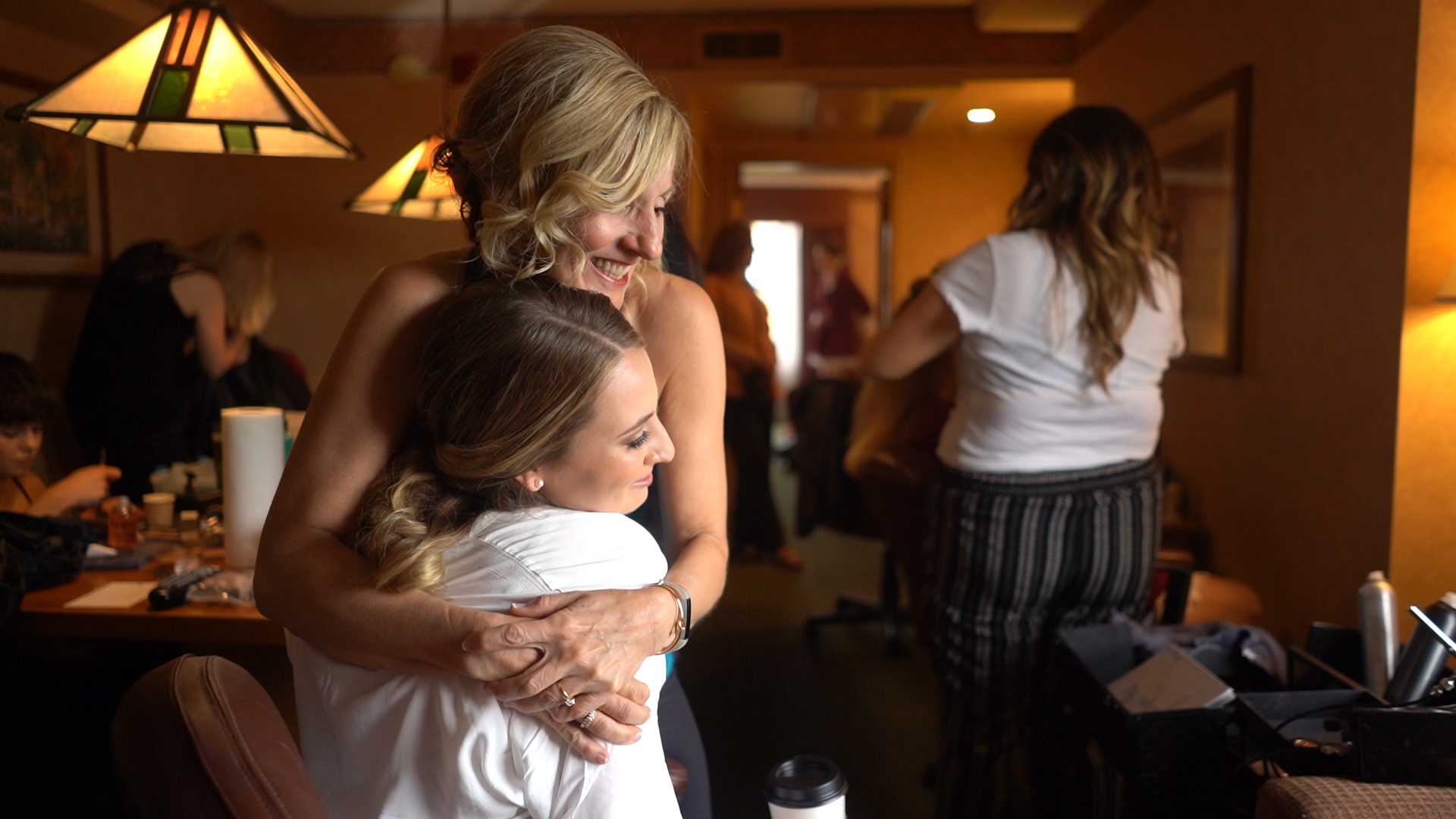 bride and mother of the bride hugging while getting ready