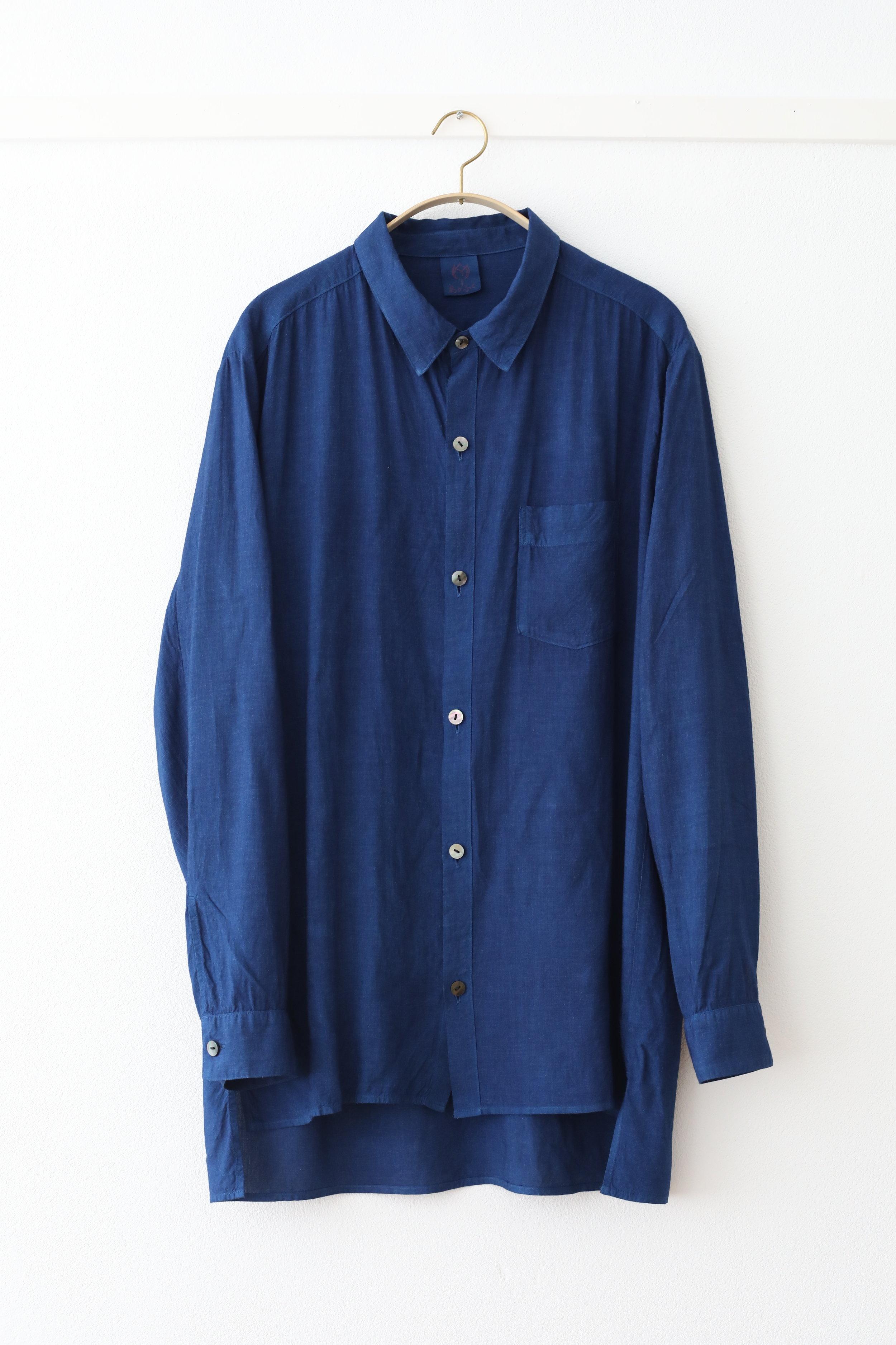 """○ ルームシャツ  堅苦しくなく素材感を生かした優しいシャツ。  素材が光沢感あり上質であるので外出時にも、ジェンダーレスにも着用できます。  シルクレーヨン素材。レーヨン(rayon)とは """"光""""のray と""""綿""""cotton を組み合わせた語源から。こちらはレーヨンテンセルという森から生まれた木材パルプを使用した再生繊維となります。  肌触りが良く涼しく、吸湿性、放湿性が良いのが特徴。藍染することで温かくなったり、より体温調節に優れています。  Made in Japan Layon : 90% , Silk : 10%  白 ¥16,000 + tax ,  正藍染 ¥27,000 + tax"""