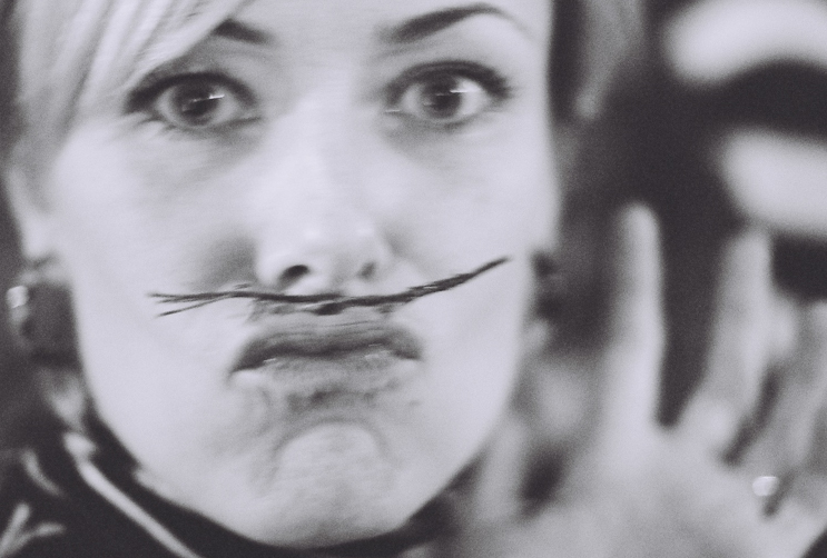 Headshot of a woman pursing her lips to hold a twig to her face
