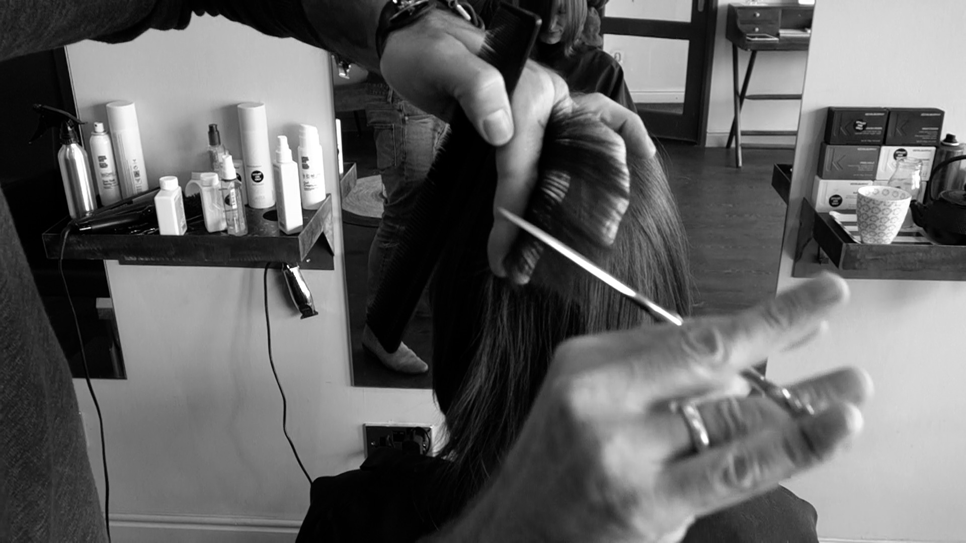 A hairdresser with scissors in hand point cutting hair