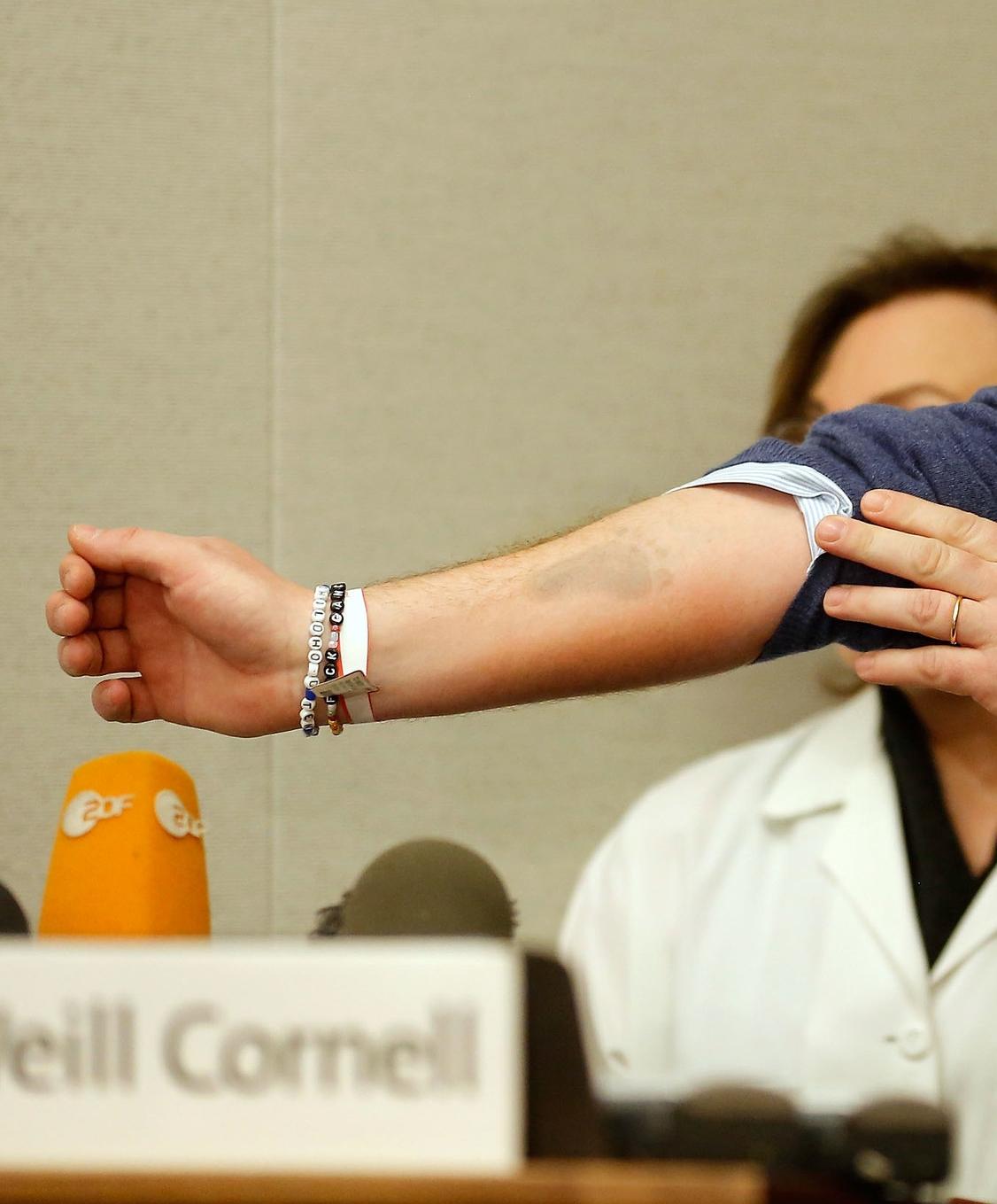 Chris hält den Armschmuck von zwei wichtigen Hilfsorganisationen in die Kamera und macht so Werbung für den guten Zweck   Foto: Getty Images