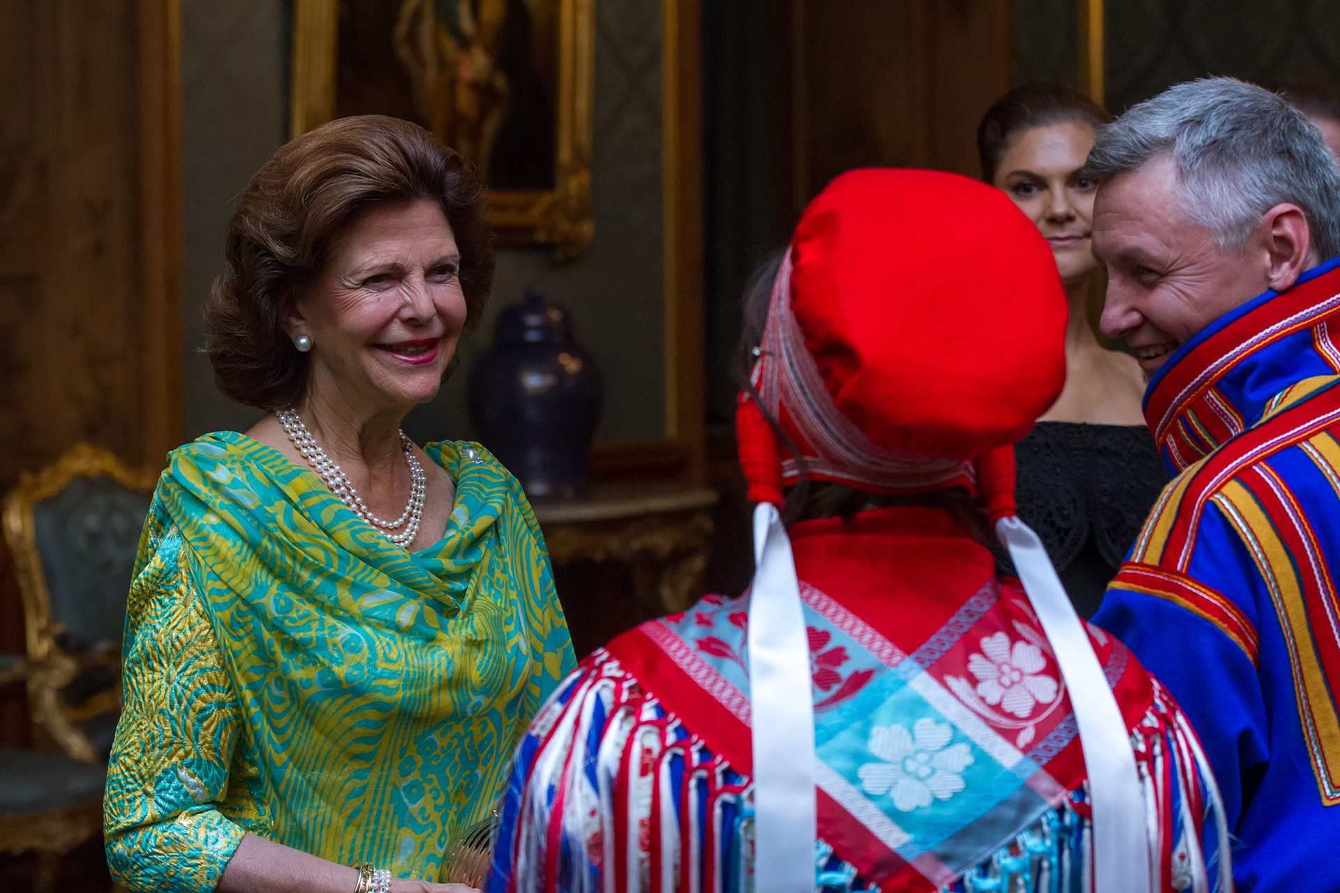 Königin Silvia begrüßt ihre ebenso farbenfroh gekleideten Gäste.  © Henrik Garlöv/Kungahuset.se