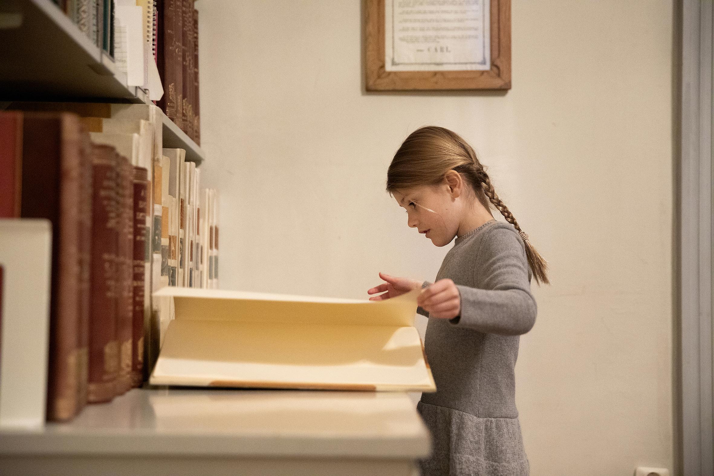 Die kleine Prinzessin stöbert in einem alten Buch über die Familiengeschichte.  ©Sara Friberg, Kungl. Royal Court