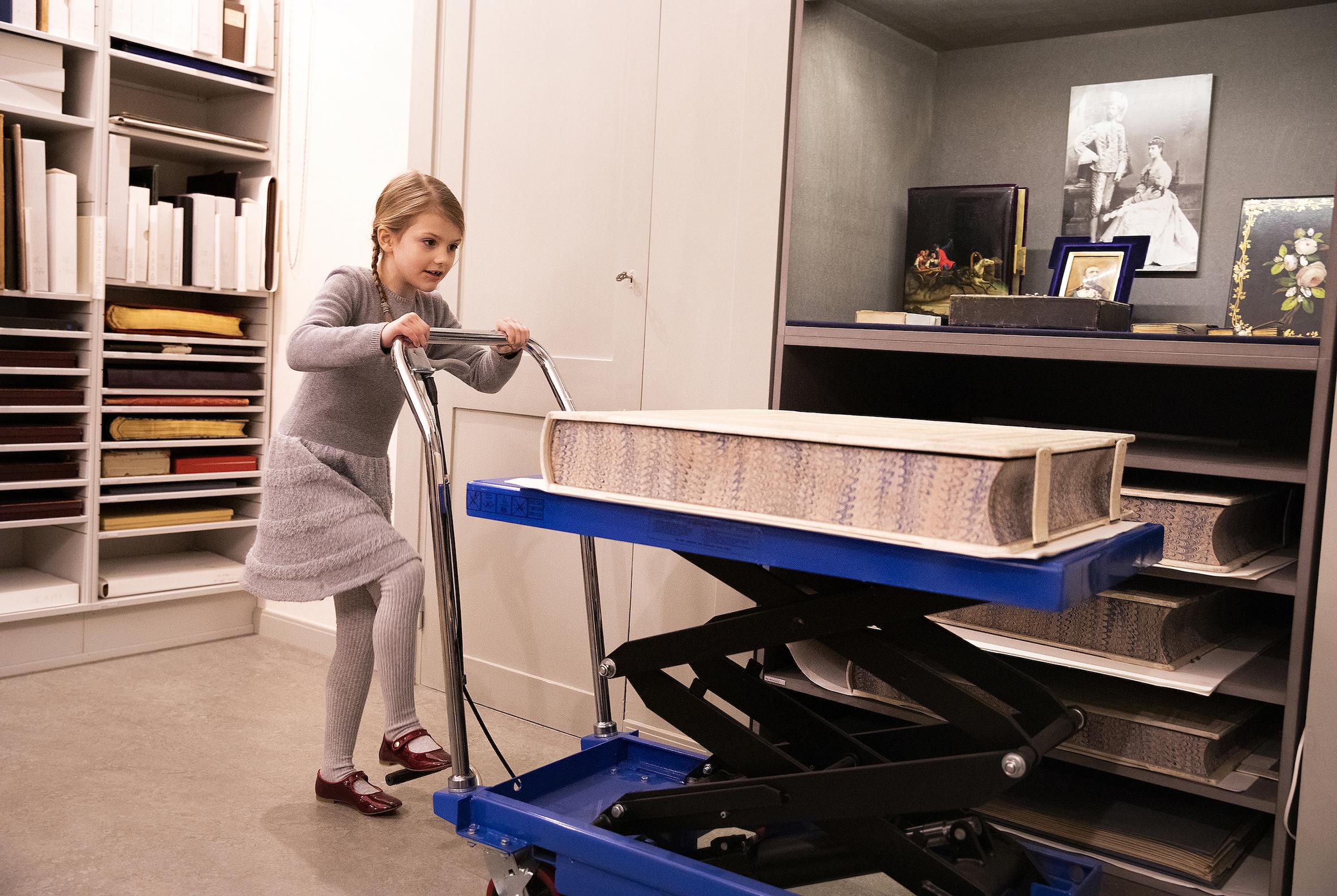 Die Schülerin transportiert ein Buch mit einem Wagen, was ihr sichtlich Spaß bringt.  ©Sara Friberg, Kungl. Royal Court