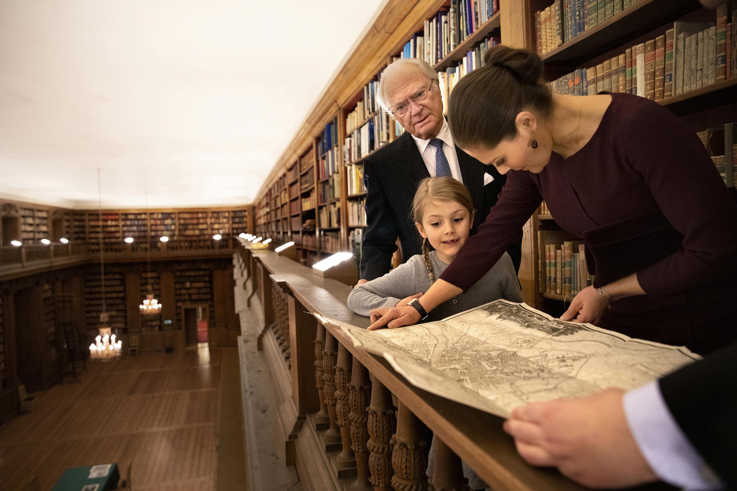 Die drei Royals schauen sich einen Stadtplan aus dem Jahr 1818 an.  ©Sara Friberg, Kungl. Royal Court