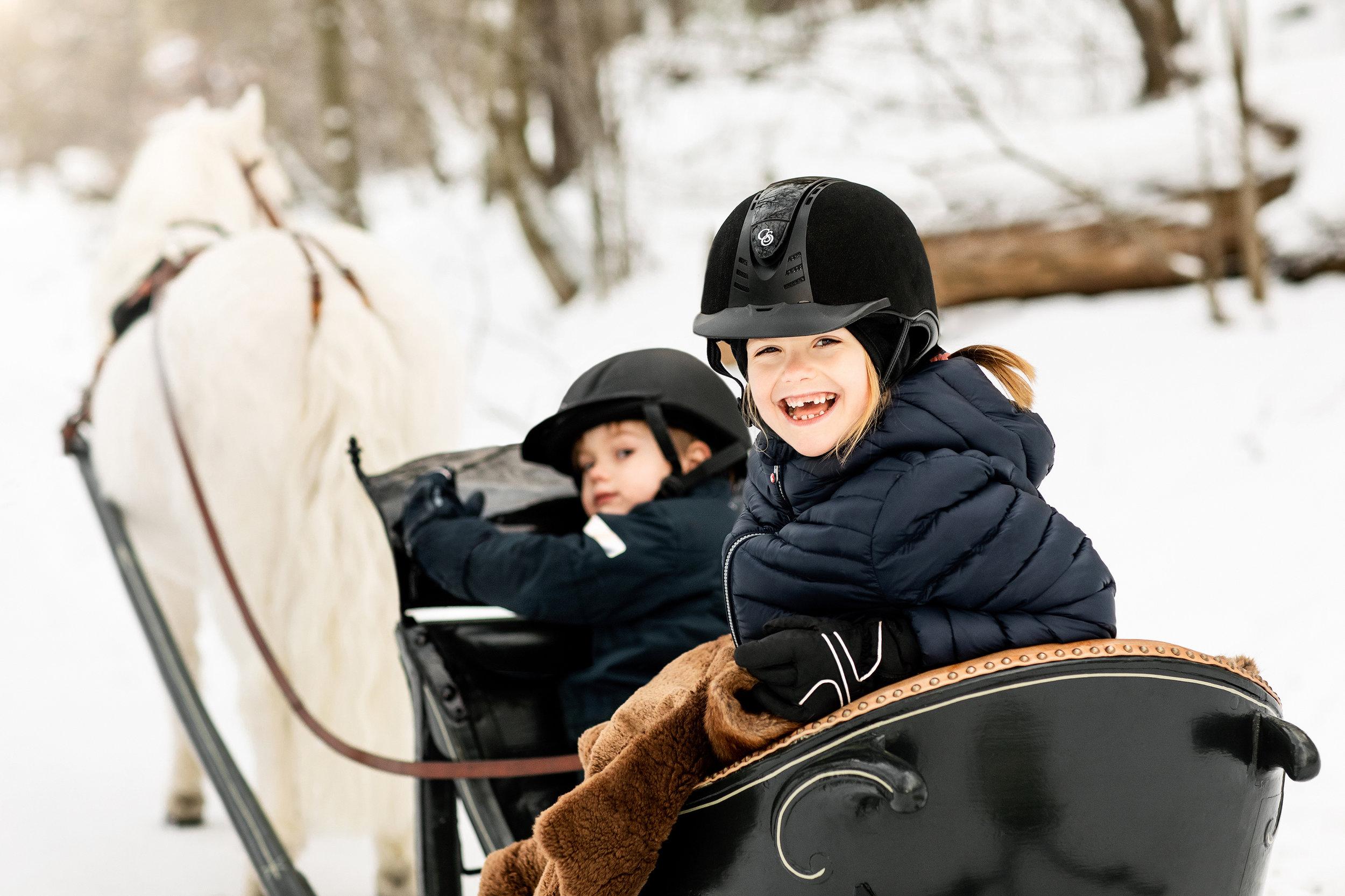 Warm eingekuschelt fahren Prinzessin Estelle und Prinz Oscar mit dem Schlitten. Die Siebenjährige strahlt über das ganze Gesicht. ©Linda Broström/Kungl. Hovstaterna