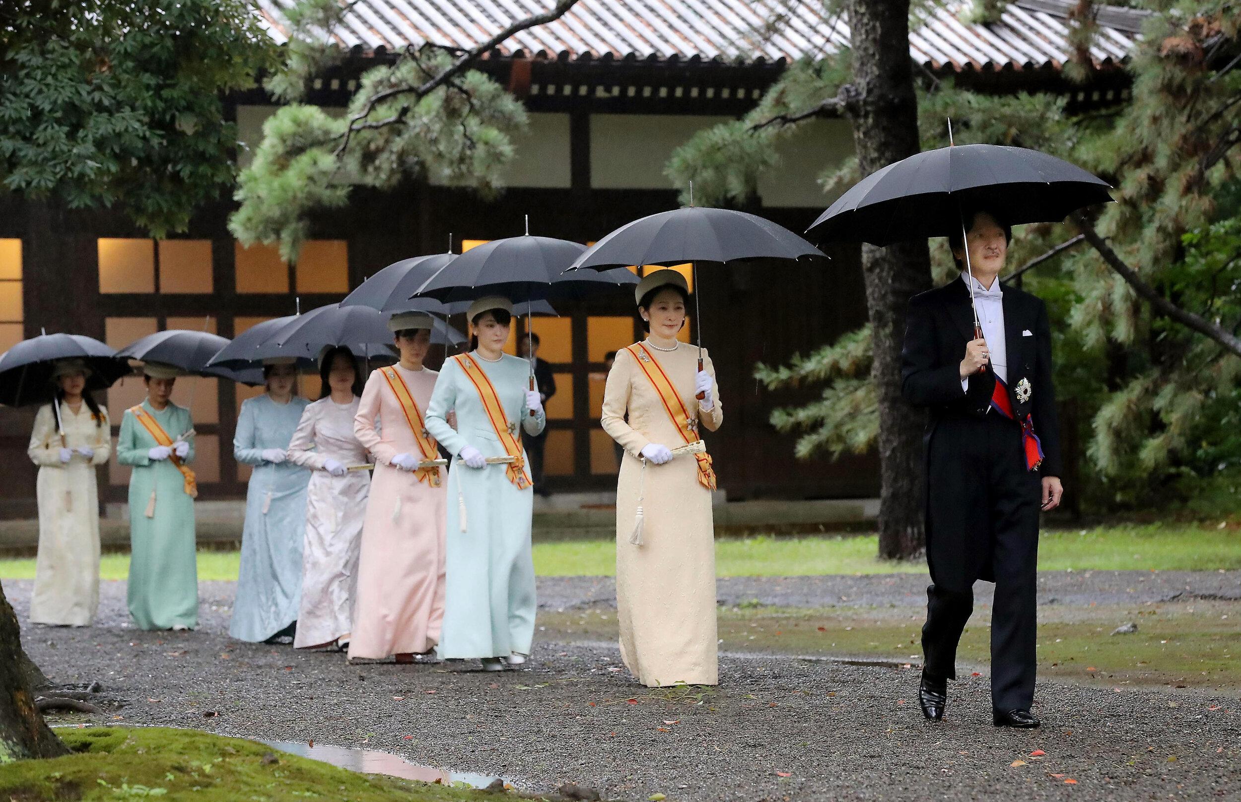 """Angeführt von Kronprinz Akishino und Kronprinzessin Kiko macht sich die japanische Kaiserfamilie auf den Weg in einen der drei Schreine des Kaiserpalastes, um an der """"Kashikodokoro""""-Zeremonie teilzunehmen.  © picture alliance / AP Photo"""