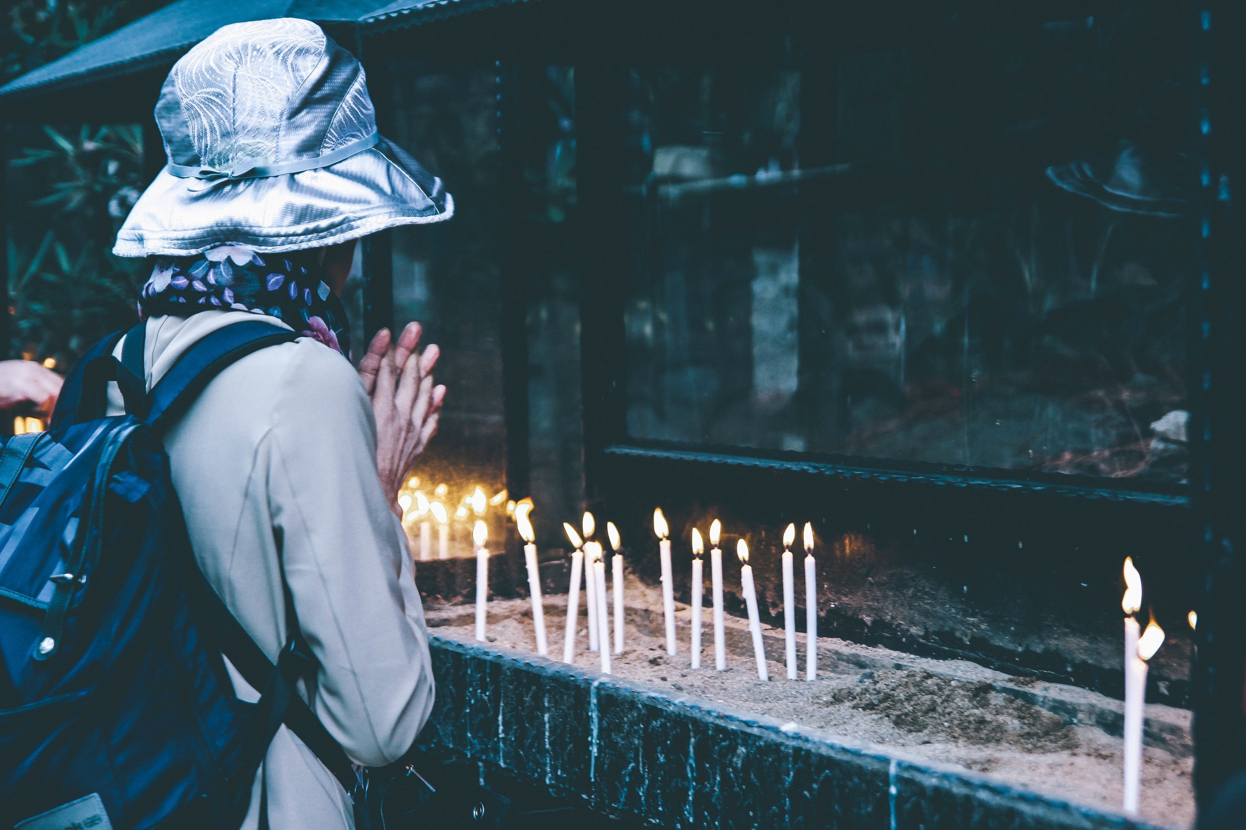 woman praying with candles.jpeg