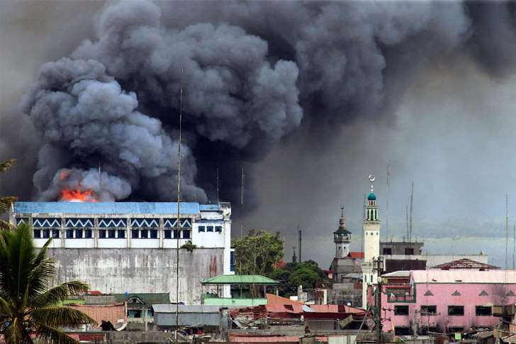 Smoke billows from a bombed out building in Marawi City. Source: Mark Jhomel /  Wikimedia