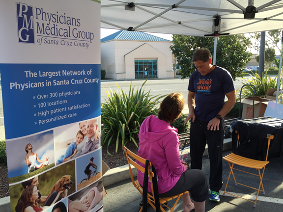 Dr. Hopkins giving foot checks outside of Whole Foods.