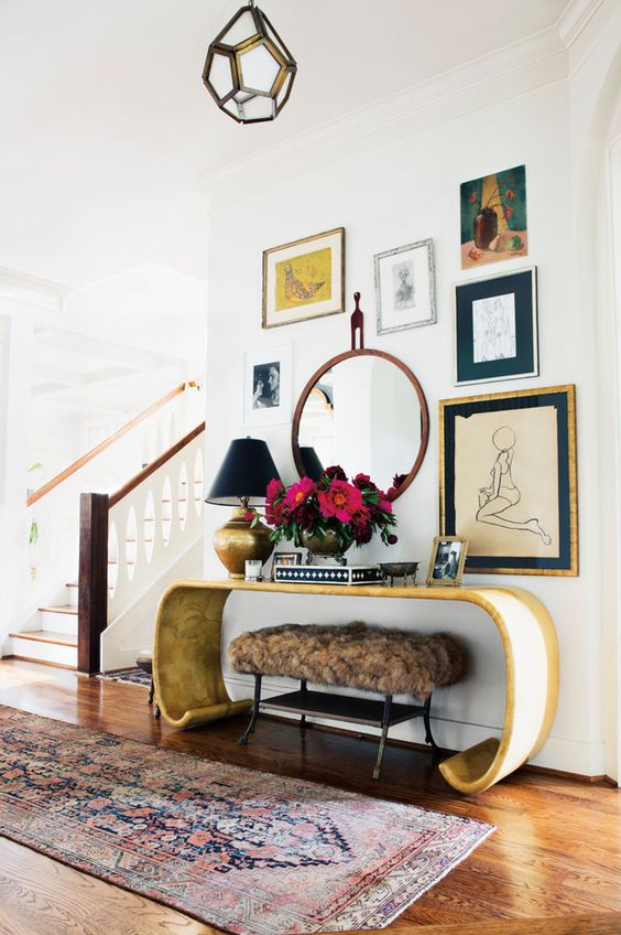 Hit your local Vintage stores and find yourself a statement Console Table like this. Also, the Gallery Wall is another statement.  Source