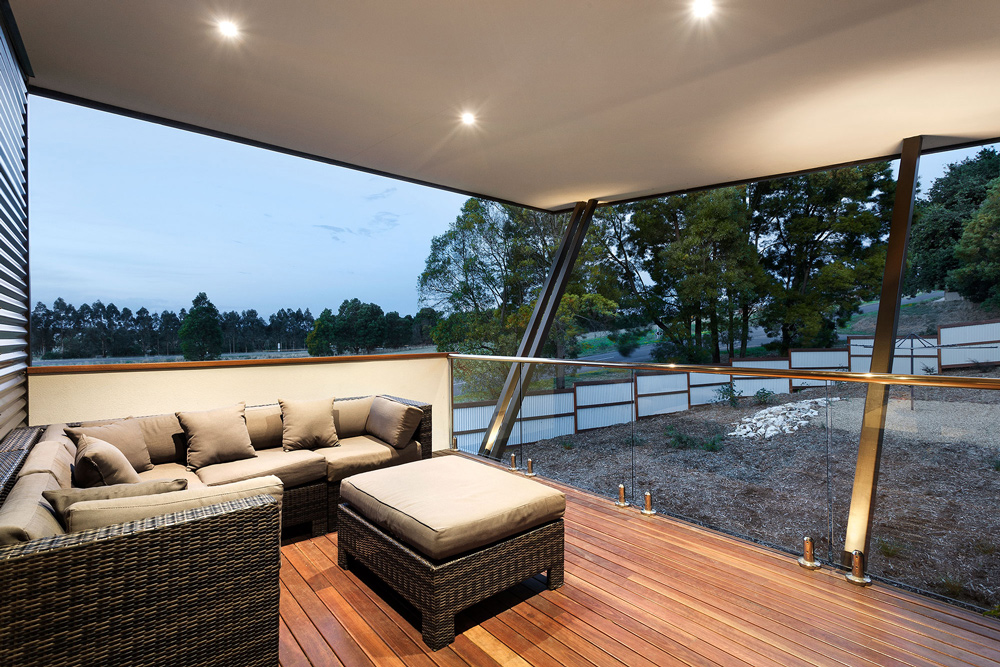 Covered outdoor entertaining area of this luxury home offering landscape views