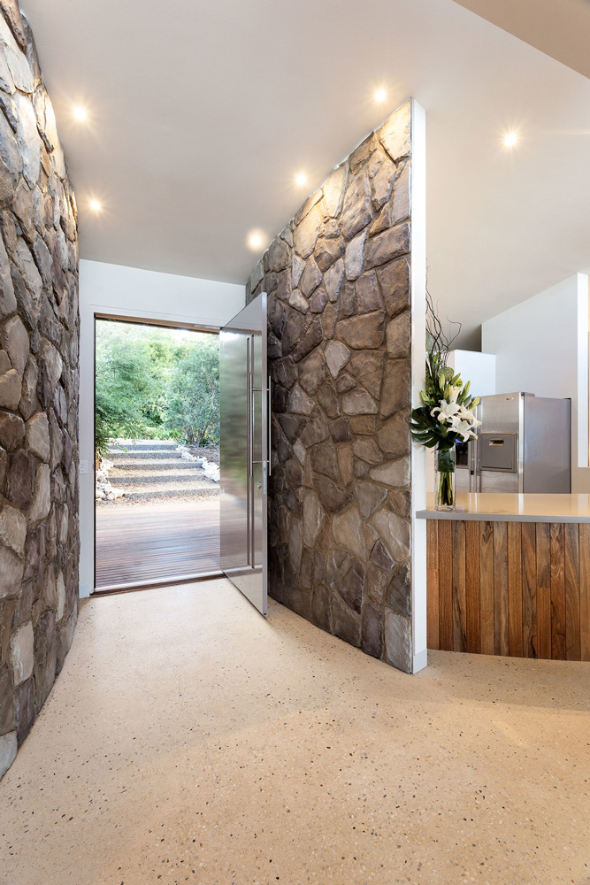 Stone entryway facade with recessed lighting above