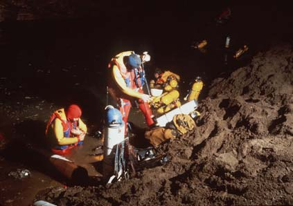 Pat Wiedeman (left), Bob Jefferys, and John Zumrick kit up at Sump 3. This was the first extensive use of composite tanks for cave diving (the dive at the San Agustin Sump in April 1981 was the only previous effort to use this technology). The team used 72 of the composite vessels (manufactured by Acurex [now EFIC]) to traverse six sumps and 4.2 kilometers of dry cave galleries separating the sumps. Sump 3 was 190 meters in length and reached a maximum depth of 22 meters. [photo �1984 Bill Stone]