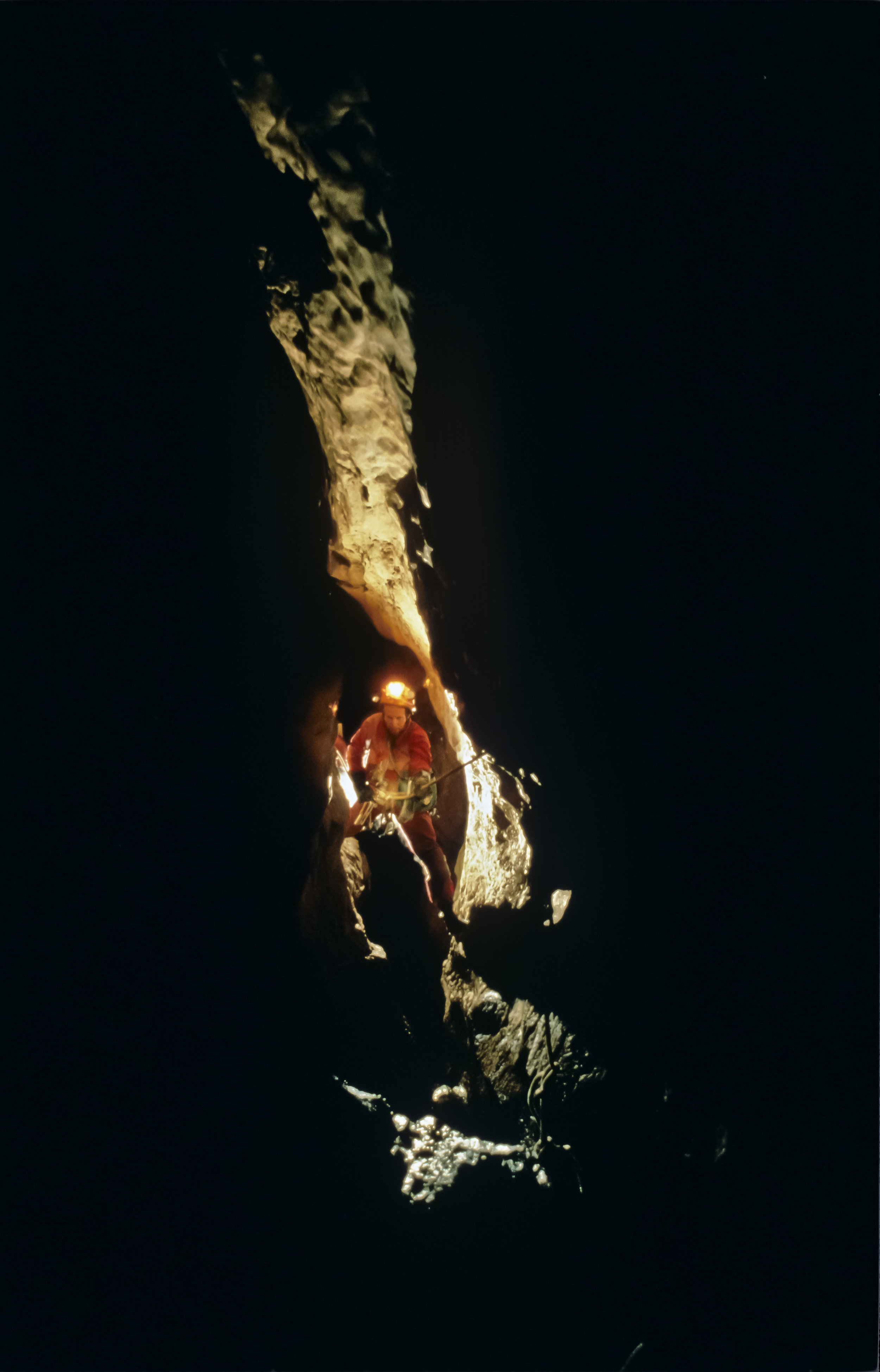 """Edging out over the abyss, Steve Porter begins a descent of """"The 100m Shaft"""", first in a series of deep pitches which descend more than 300m with very little horizontal offset. Photo by U. S. Deep Caving Team/Wes Skiles."""