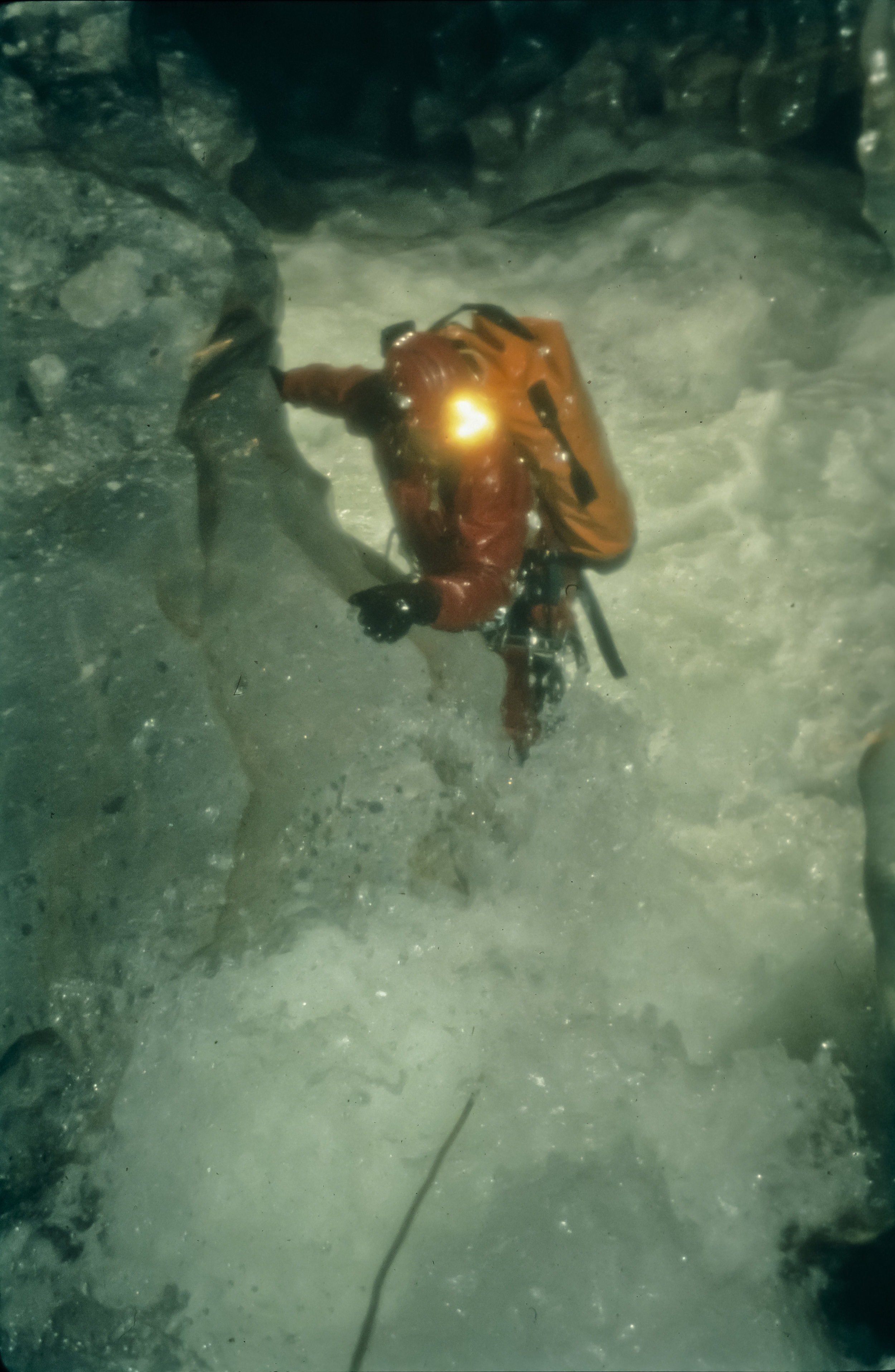 "The National Geographic caption for this slide read ""Torrent from a freak April storm erupts into the Upper Gorge, below which seven team members had camped. Getting his grip with rubberized gloves, Noel Sloan fights thundering white water six feet above normal"". Photo by U. S. Deep Caving Team/Wes Skiles."