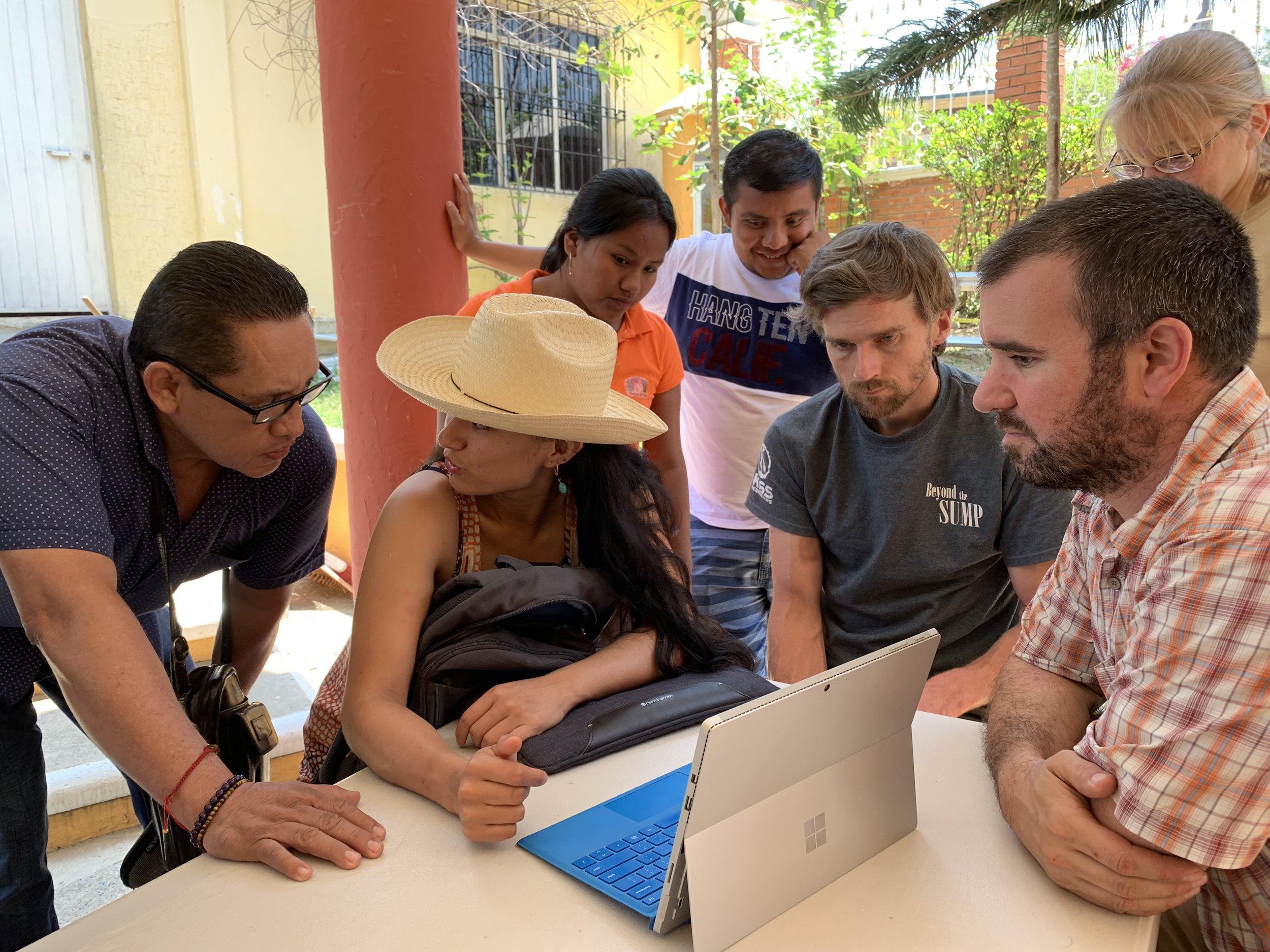 Alejandra Mendoza, Jon Lillestole, and Zeb Lilly showinf expedition photos to locals of San Felipe Jalapa de Díaz. Photo by Teddy Garlock.