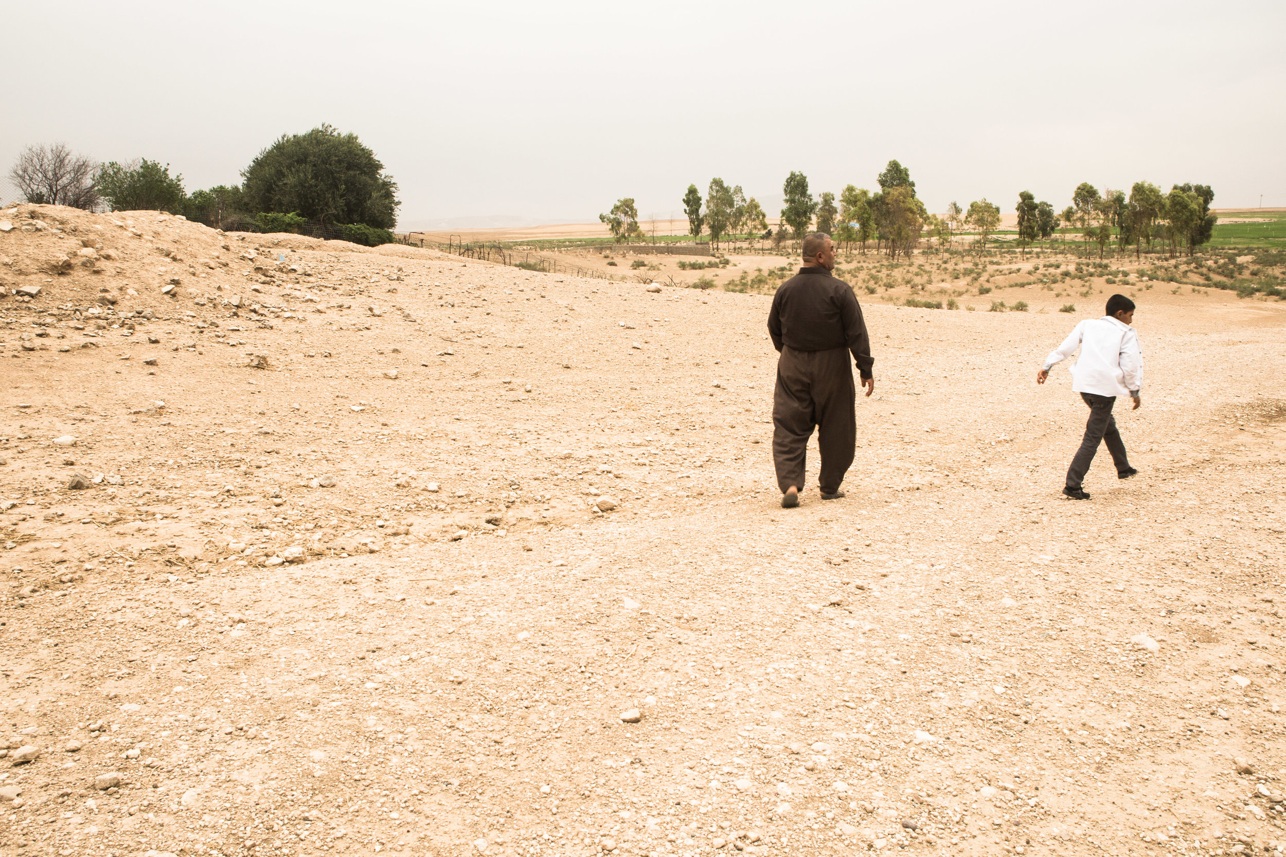 Samed Ismael Ali walks with his son back to their home in Gara Sur.