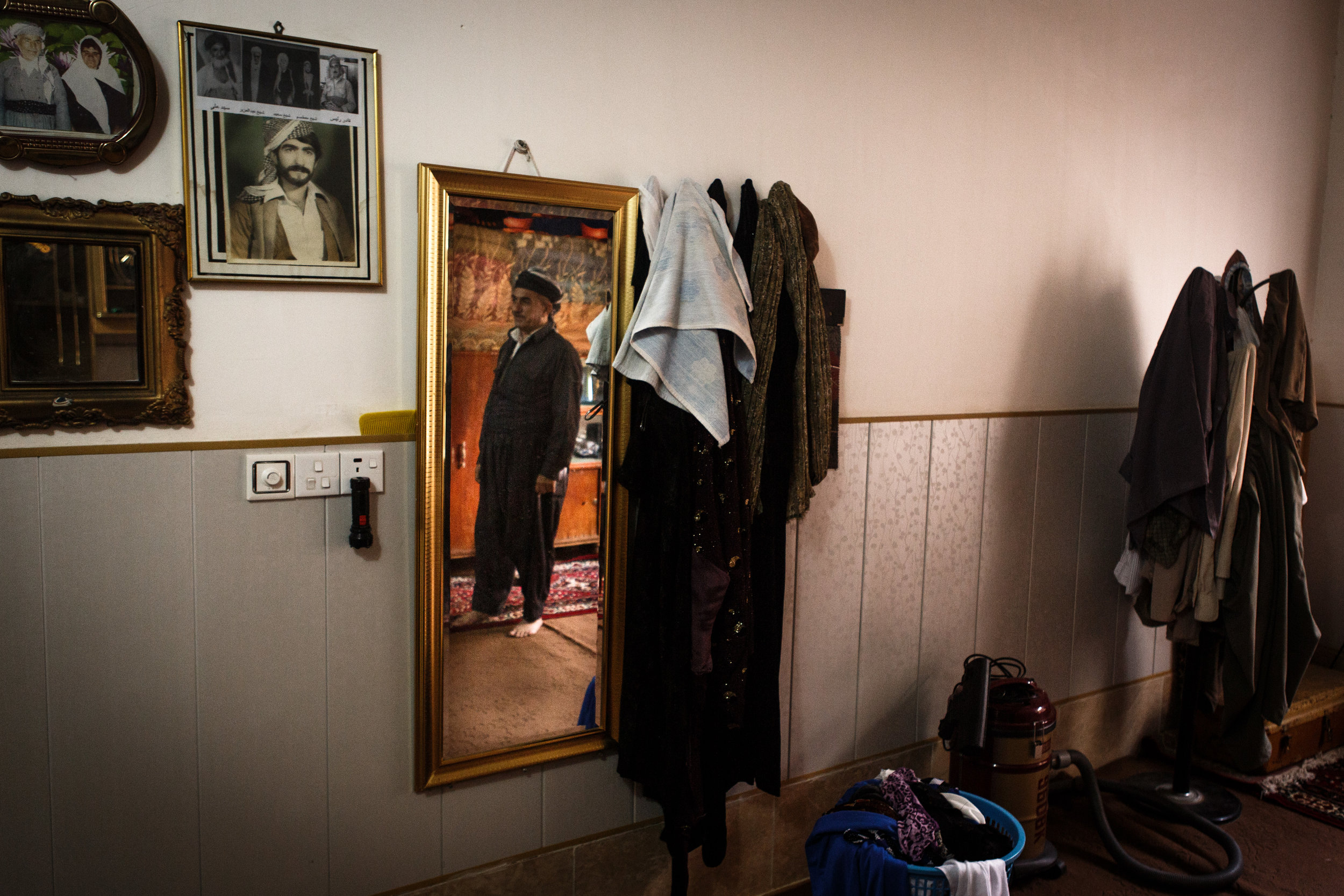 A reflection of Abdul Kadr Muhammed is seen on a mirror inside the family's bedroom in Busheon.